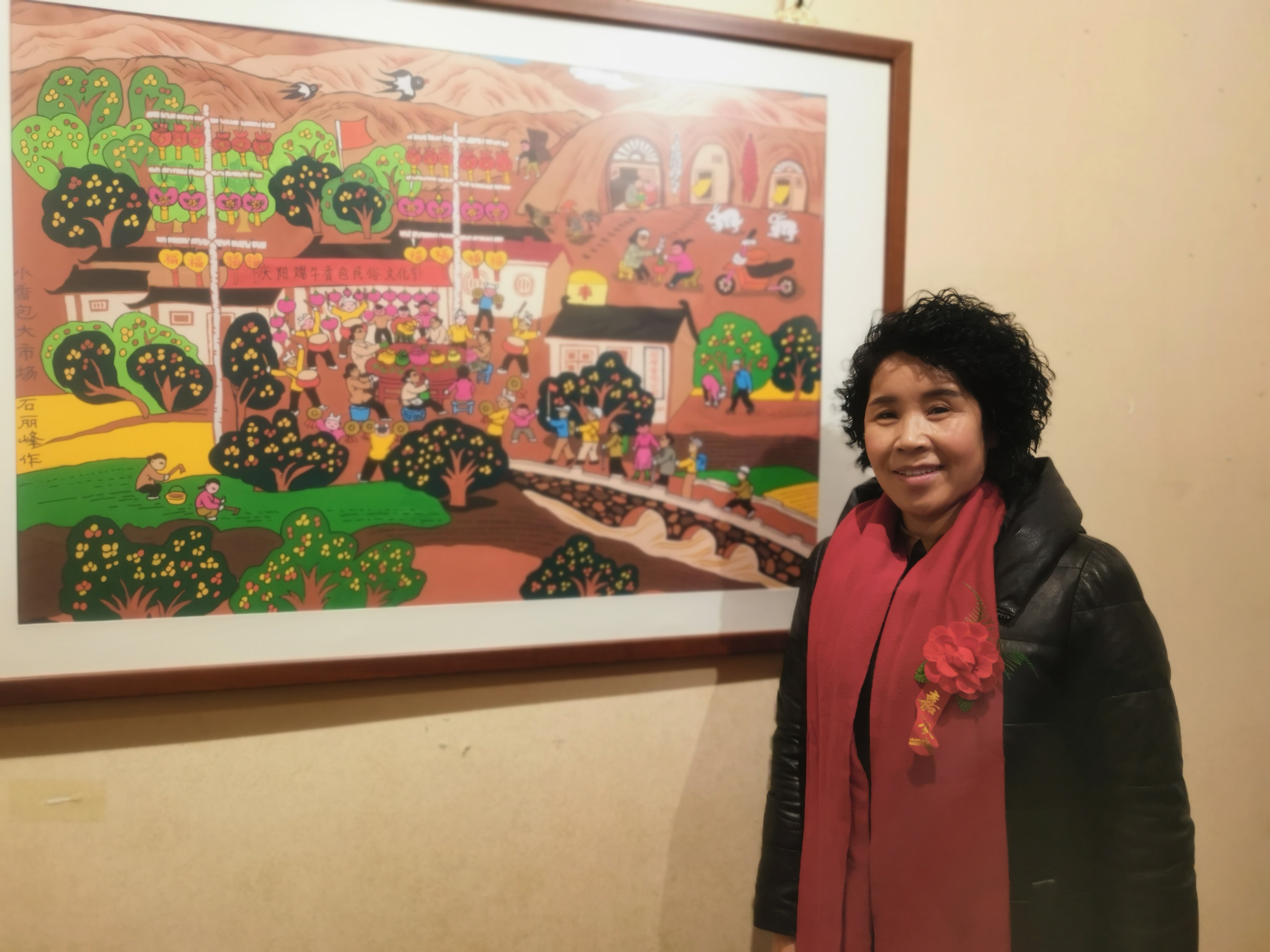 石麗峰的作品也參加了此次畫展,作為甘肅慶陽人的她既是一名農民畫家也是一名香包刺繡藝人。畫展上,石麗峰介紹,她的作品名為《脫貧致富的好產業》,最近才完成。反映的是一個農村婦女傳承香包製作工藝,全國各地的遊客前來觀摩,展現了黃土高原獨特的民俗文化和原生態的黃土風情。圖為石麗峰和她的作品《脫貧致富的好產業》。