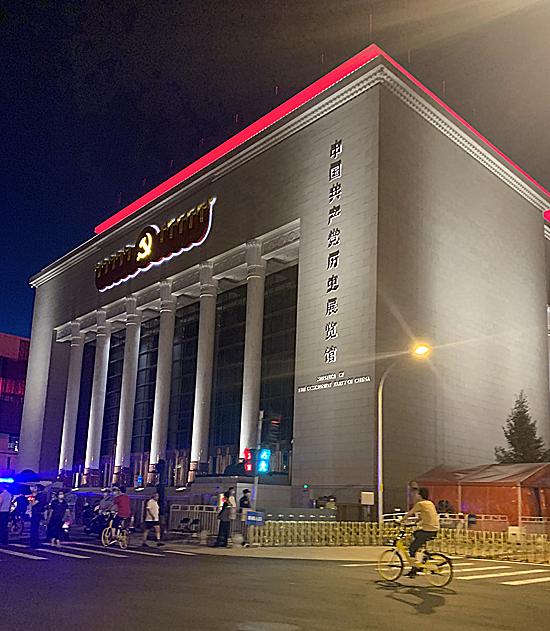 夜晚的展覽館在燈光的映襯下愈加顯得光彩奪目,每一根廊柱在光柱的照耀下愈加挺拔向上,簡約質樸的頂冠部分是大氣的中國紅,而在十面黨旗的中心是金黃色燈光的中國共產黨黨徽,頗具歷史的莊重感。