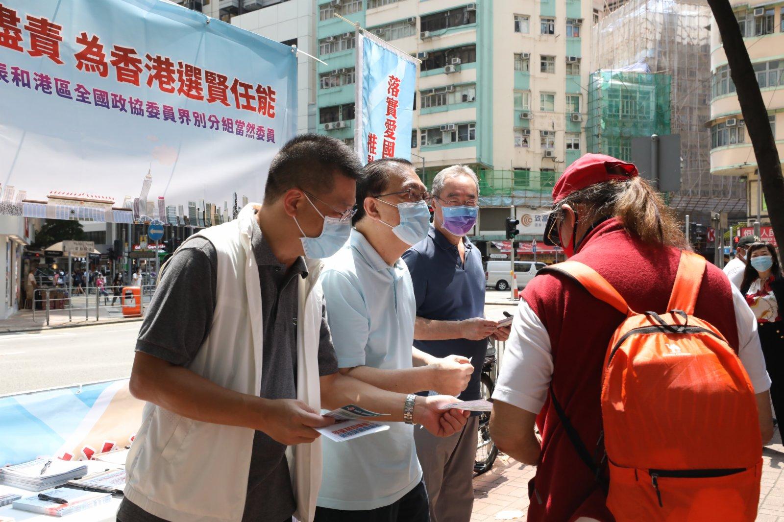 譚耀宗(左二)落區向市民宣傳「愛國者治港」。(大公文匯全媒體記者萬霜靈攝)