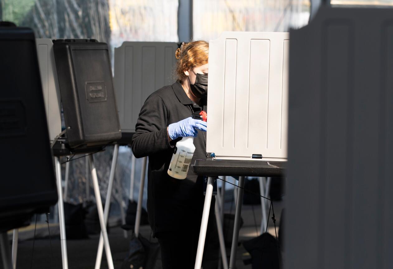 為防範新冠疫情,美國舊金山在市政廳外設立戶外投票中心,從當地時間10月5日開始為參加美國大選的選民提供服務。 10月5日,在美國舊金山市政廳戶外投票中心,一名工作人員進行清潔和消毒。(新華社)