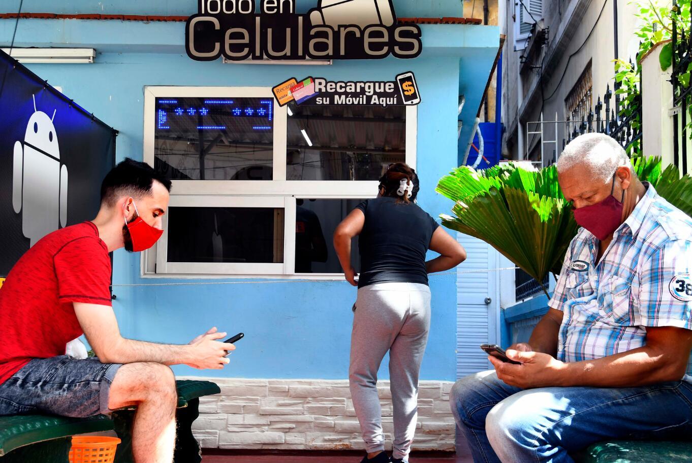10月5日,民眾戴口罩在古巴哈瓦那一家手機維修店門口等候。(新華社)