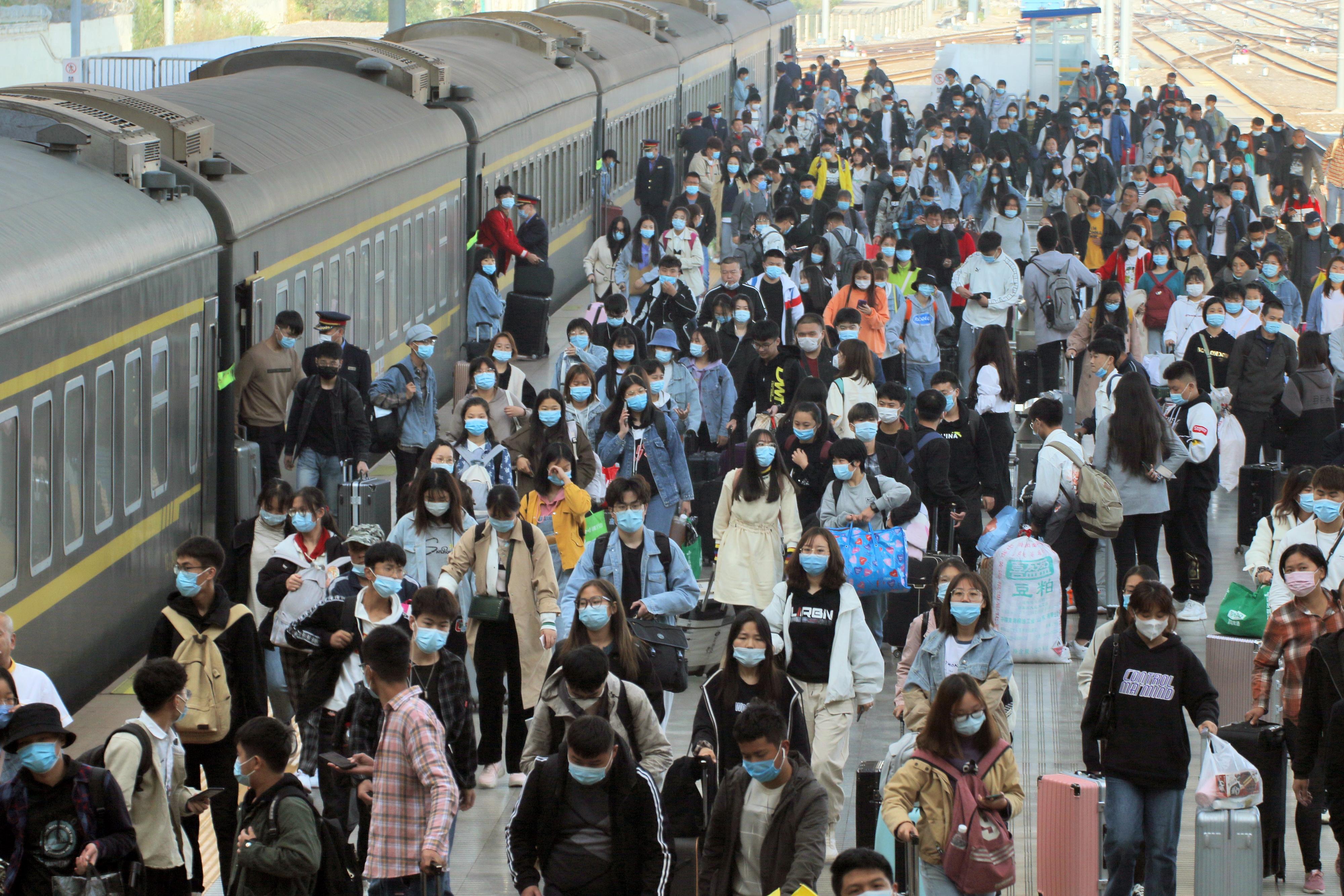 國慶長假臨近尾聲,多地交通運輸部門迎來返程客流高峰。圖為10月8日,旅客在山東煙台火車站下車出站。(新華社)