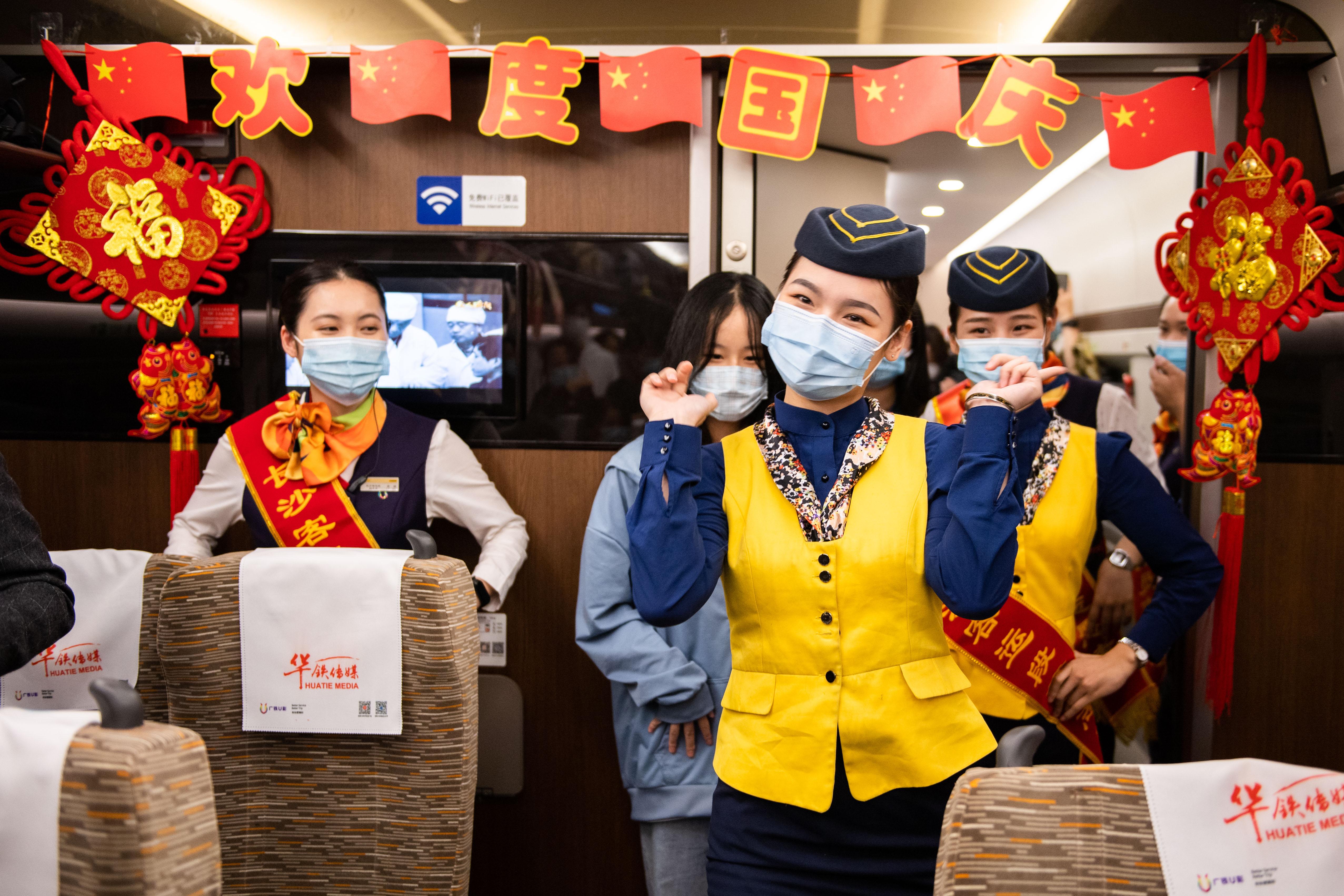 在岳陽東開往廣州南的G6131次「復興號」高鐵列車上,乘務員在「喜迎國慶濃情中秋」活動中為旅客表演舞蹈(10月1日攝)。 (新華社)