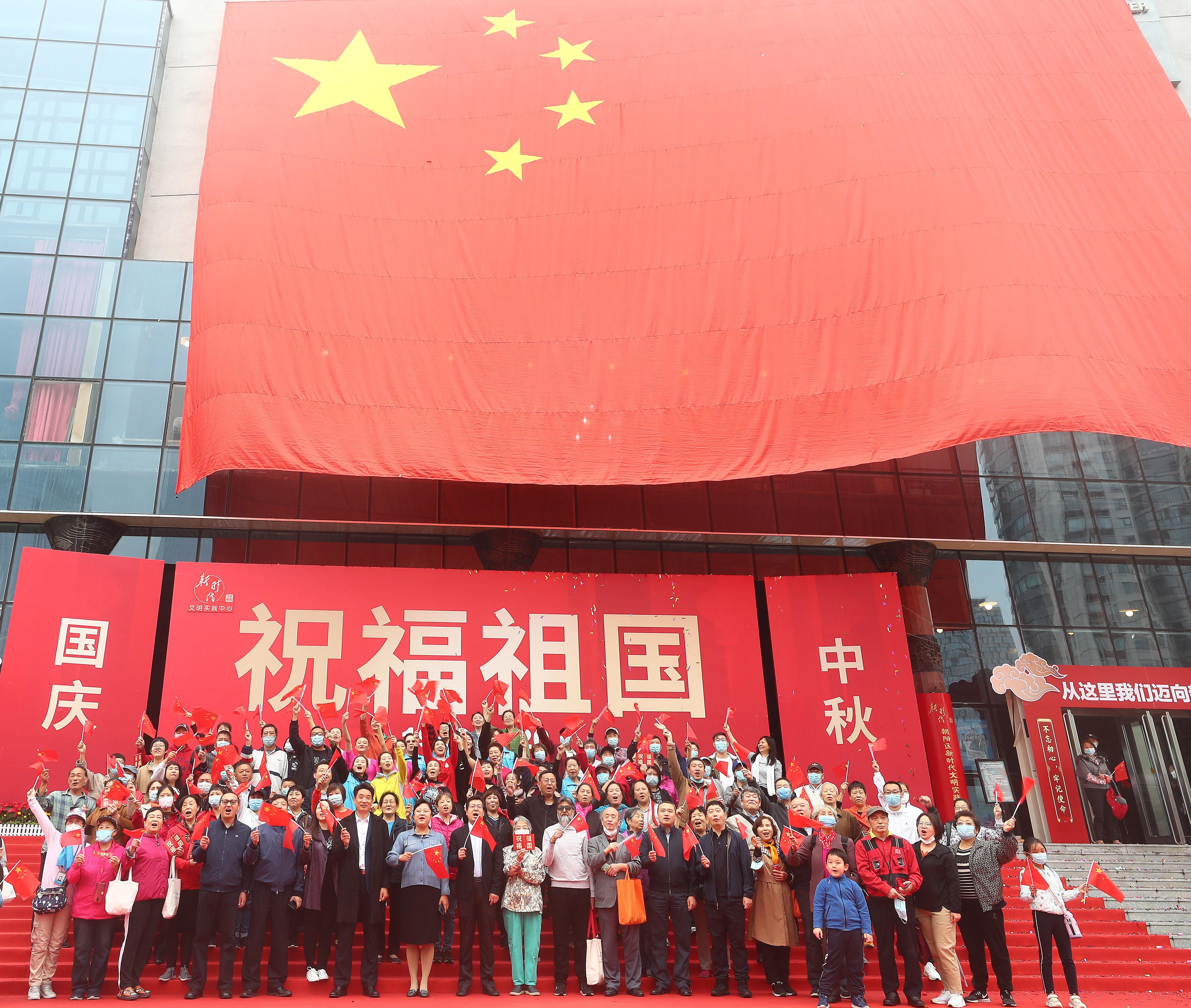 在北京市朝陽區文化館舉辦的國慶專題活動上,嘉賓與國旗合影(10月1日攝)。(新華社)