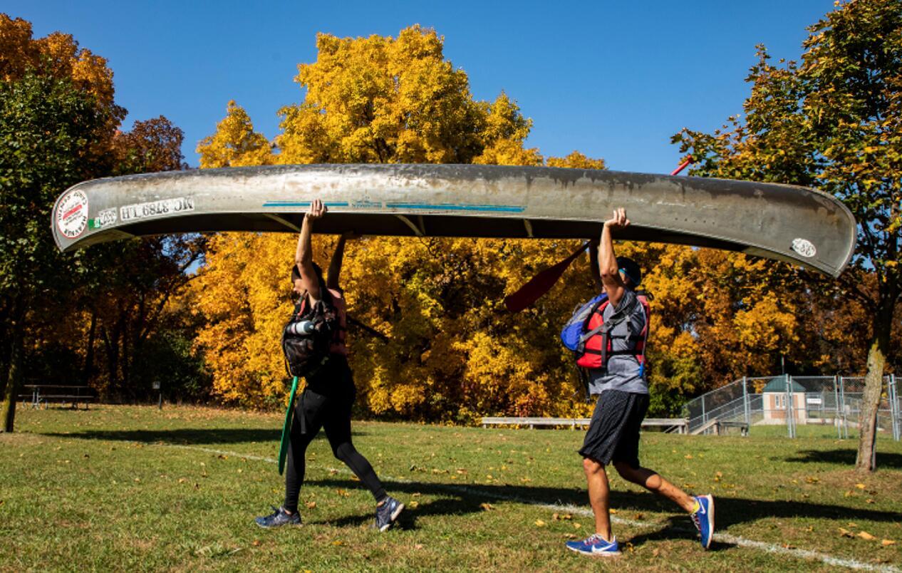 10月11日,在美國密歇根州東部利文斯頓縣,人們向河畔搬運獨木舟。(新華社)