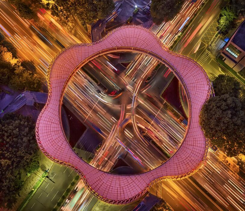 《流光花》:深圳南山區的「春花天橋」在夜幕下顯得格外的好看,猶如一朵美麗的梅花。在川流不息的車燈襯托下,繽紛絢麗。映射出南山文化新地標的撼人魅力。