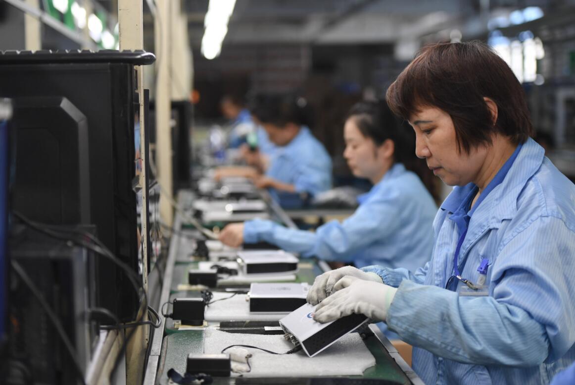 10月19日,在福州經濟技術開發區,一家通信科技企業的員工在組裝出口非洲的數字機頂盒。 (新華社)