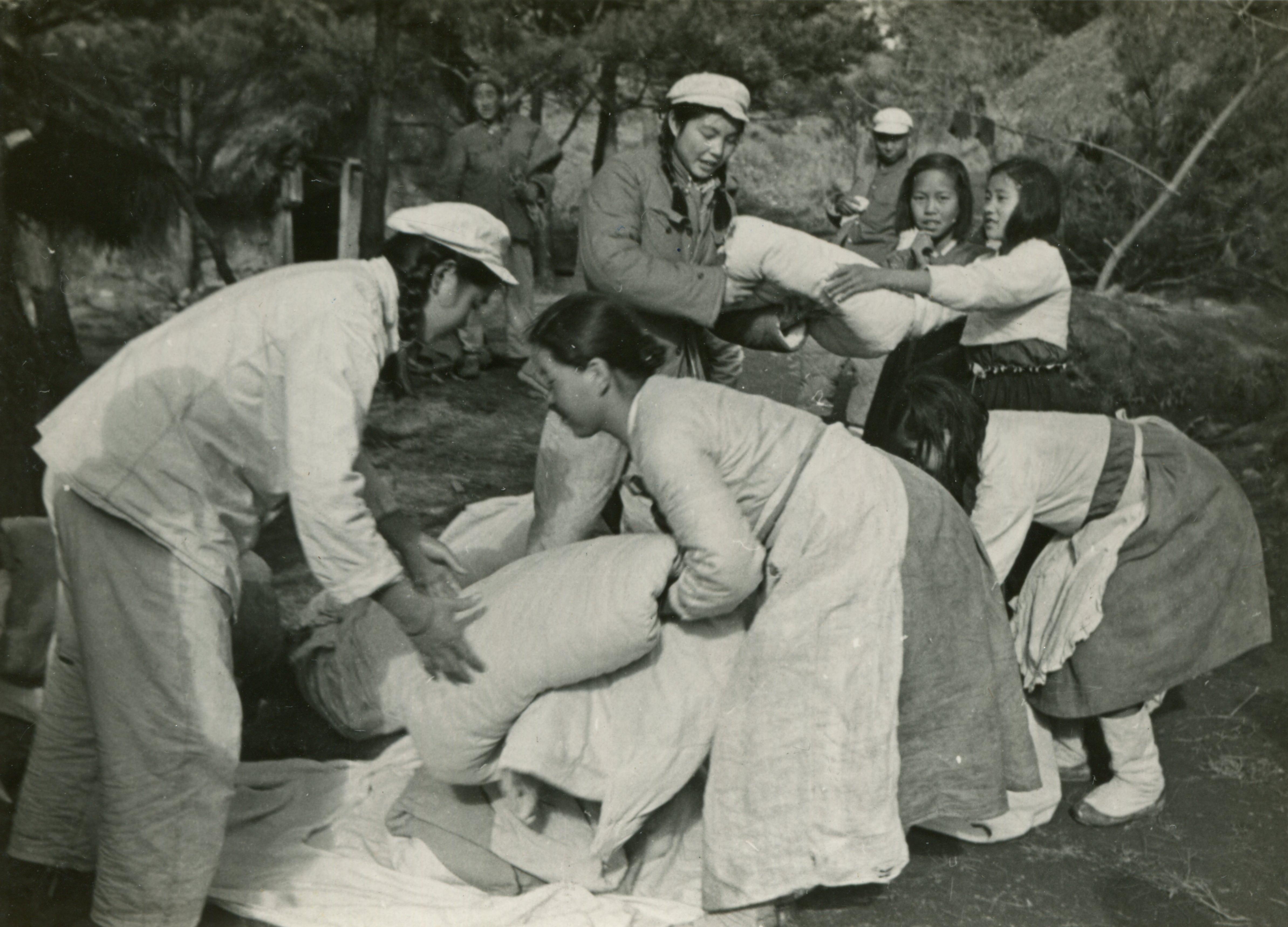 1952年12月22日, 在上甘嶺陣地,朝鮮婦女為負傷志願軍戰士換洗被褥衣服,把洗淨的被褥交給我軍護士。(資料圖片)
