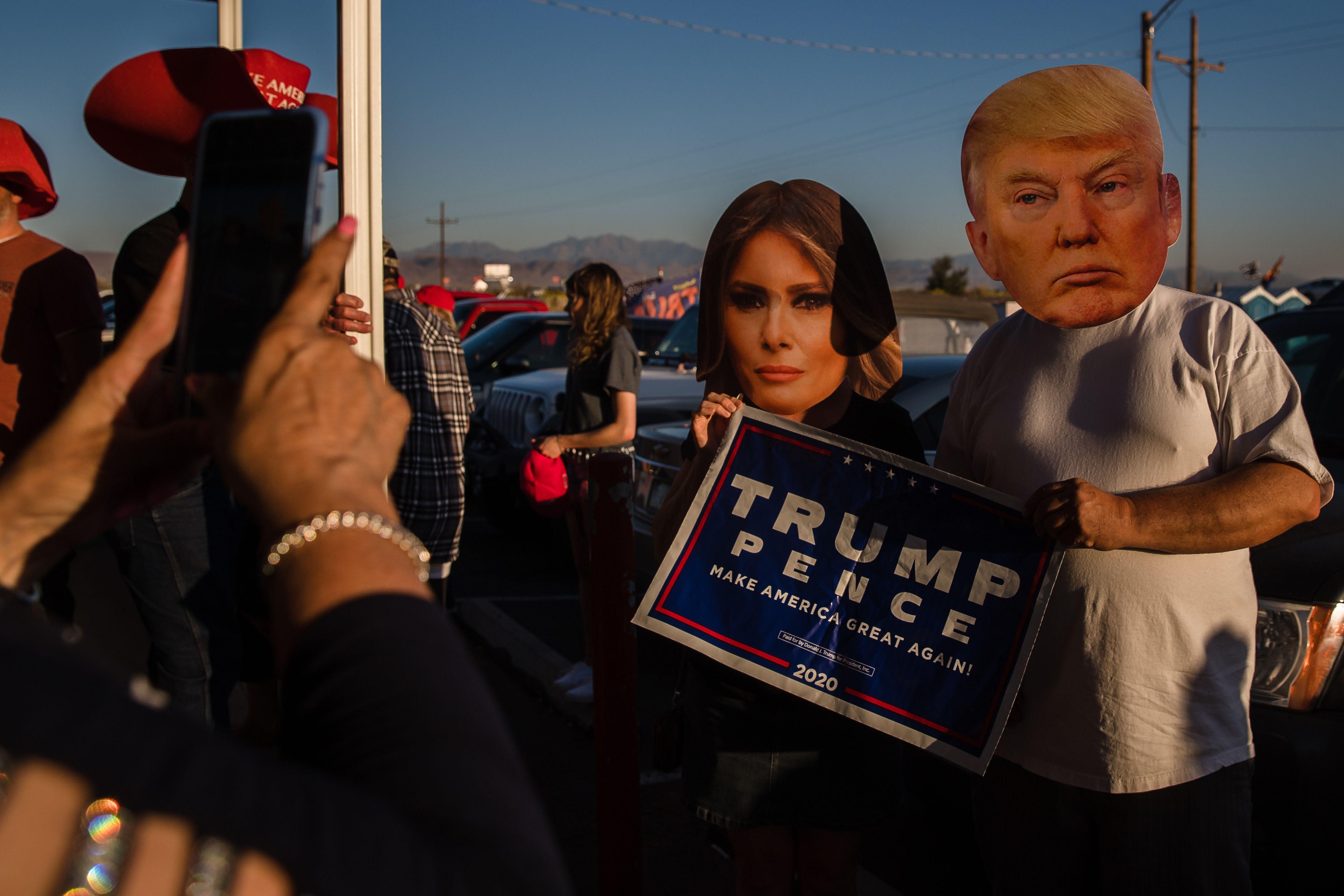 當地時間10月22日,人們聚集在亞利桑那州金谷舉行總統辯論觀察會時,一個戴着特朗普總統和梅拉尼亞總統面具的男人和女人在大美國披薩餐廳餐廳前合影。(法新社)