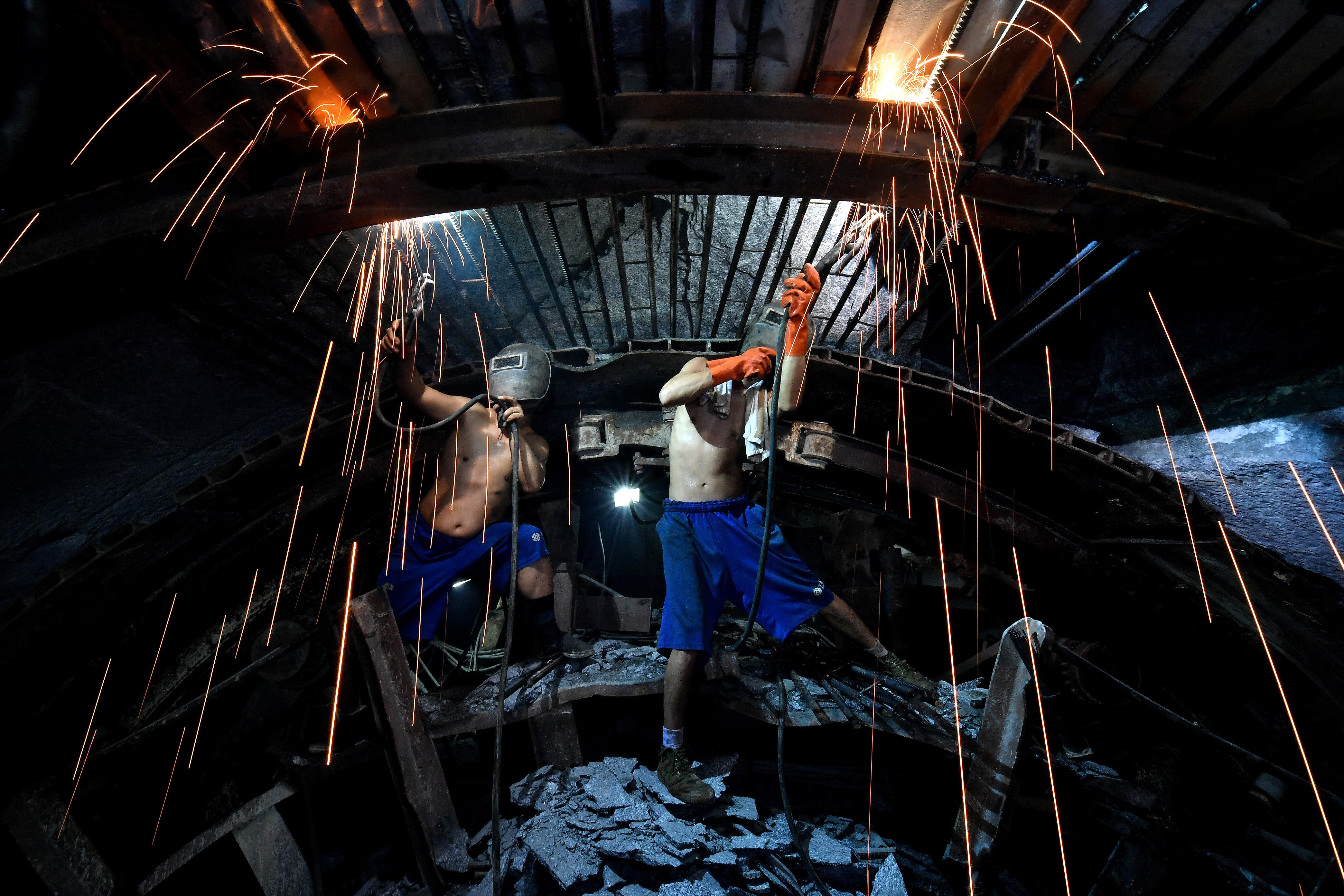 10月22日,工作人員在引漢濟渭秦嶺輸水隧洞中進行作業。該隧洞最大埋深達2012米,終年高溫潮濕。(新華社)