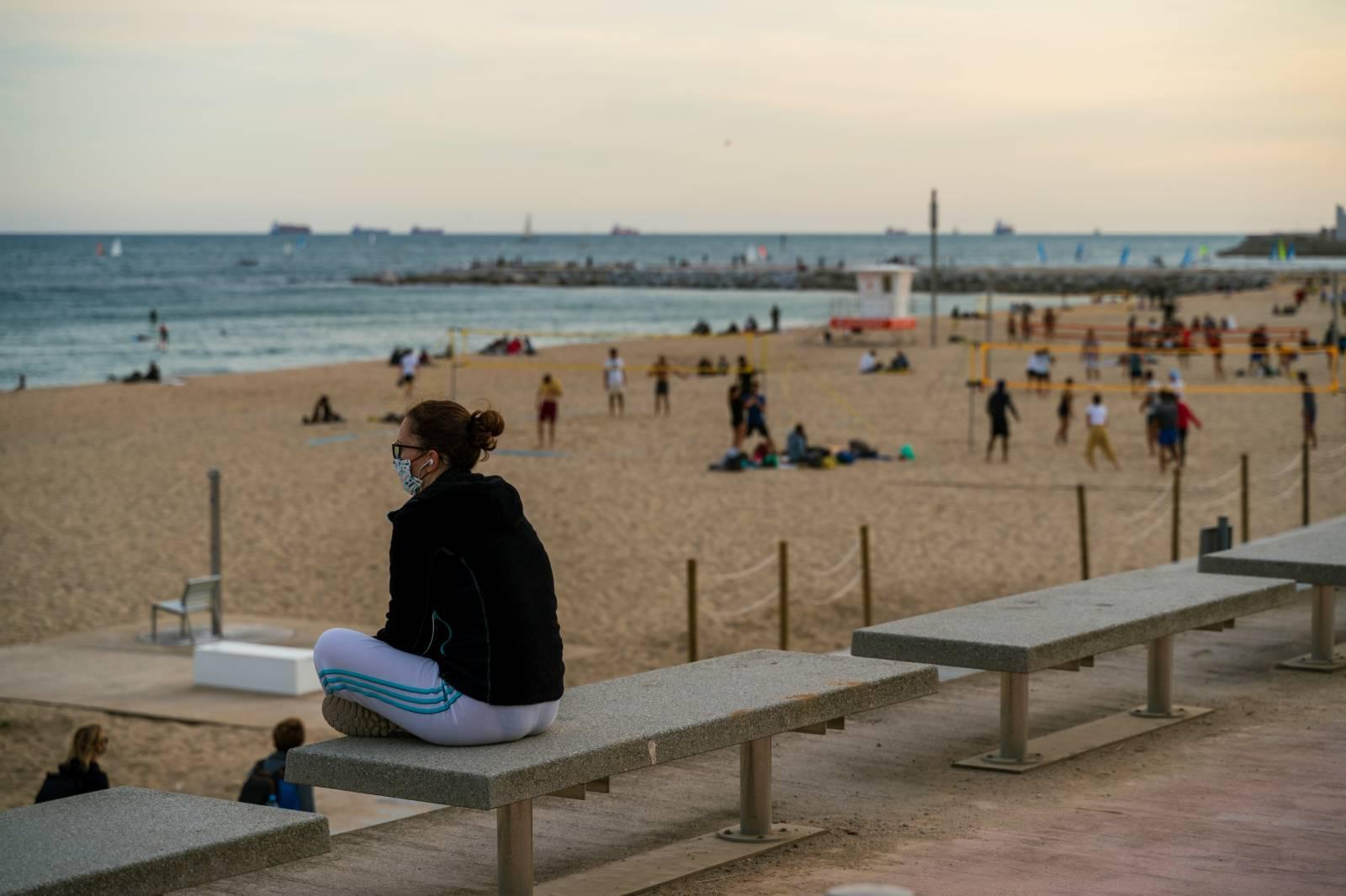10月25日傍晚,人們在西班牙巴塞羅那海邊小憩。(新華社)