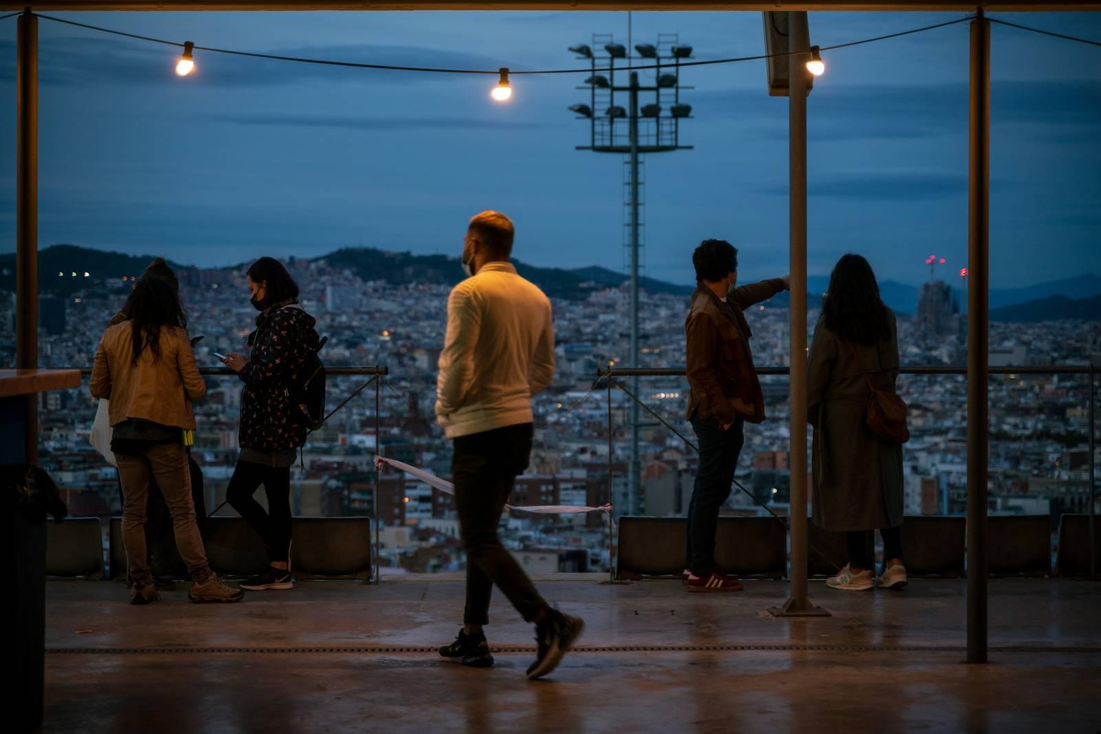 10月25日傍晚,人們在西班牙巴塞羅那欣賞夜景。(新華社)