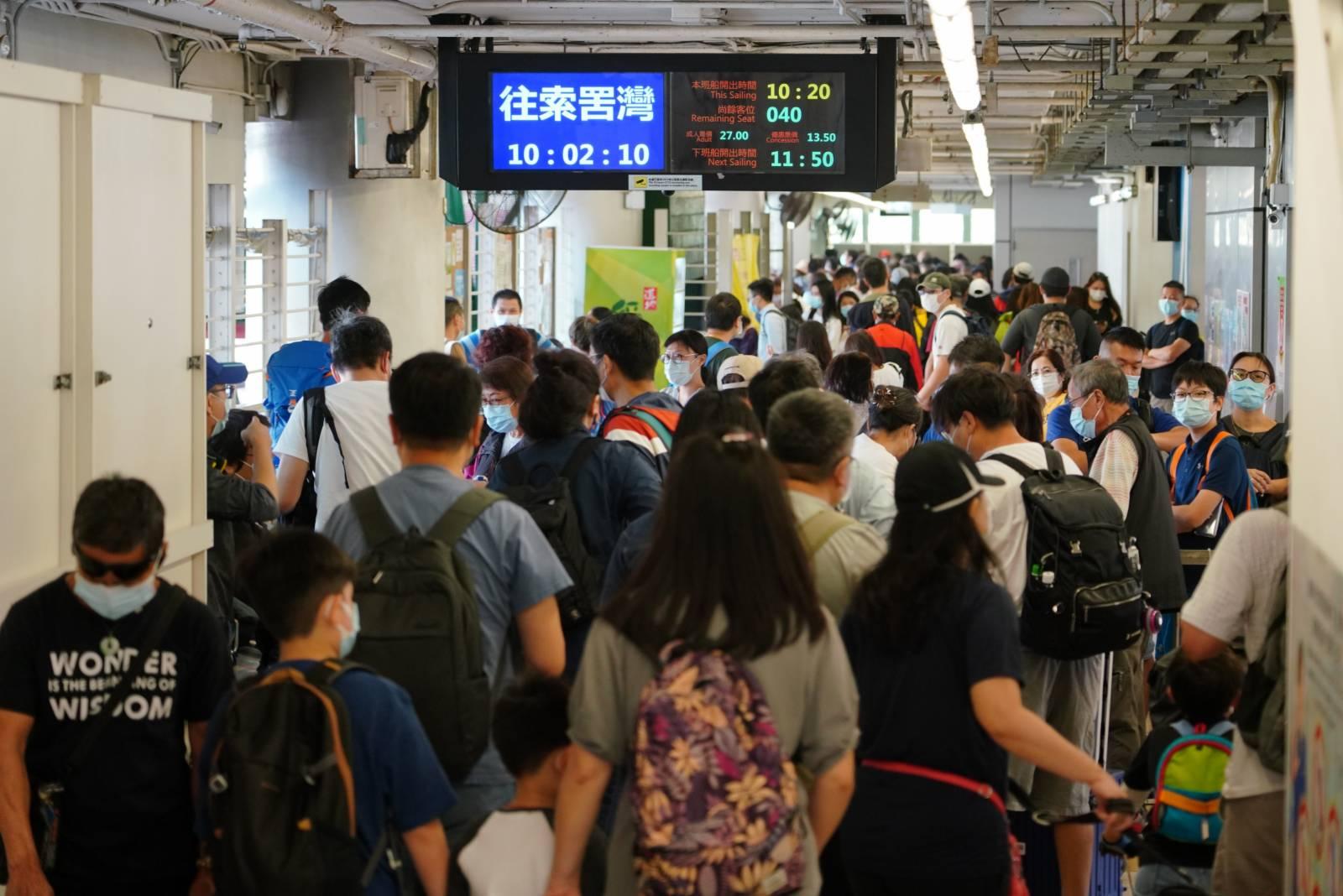 10月25日重陽節,在香港中環碼頭,前往長洲、南丫島和大嶼山等地的市民在碼頭排起長龍。(中新社圖片)