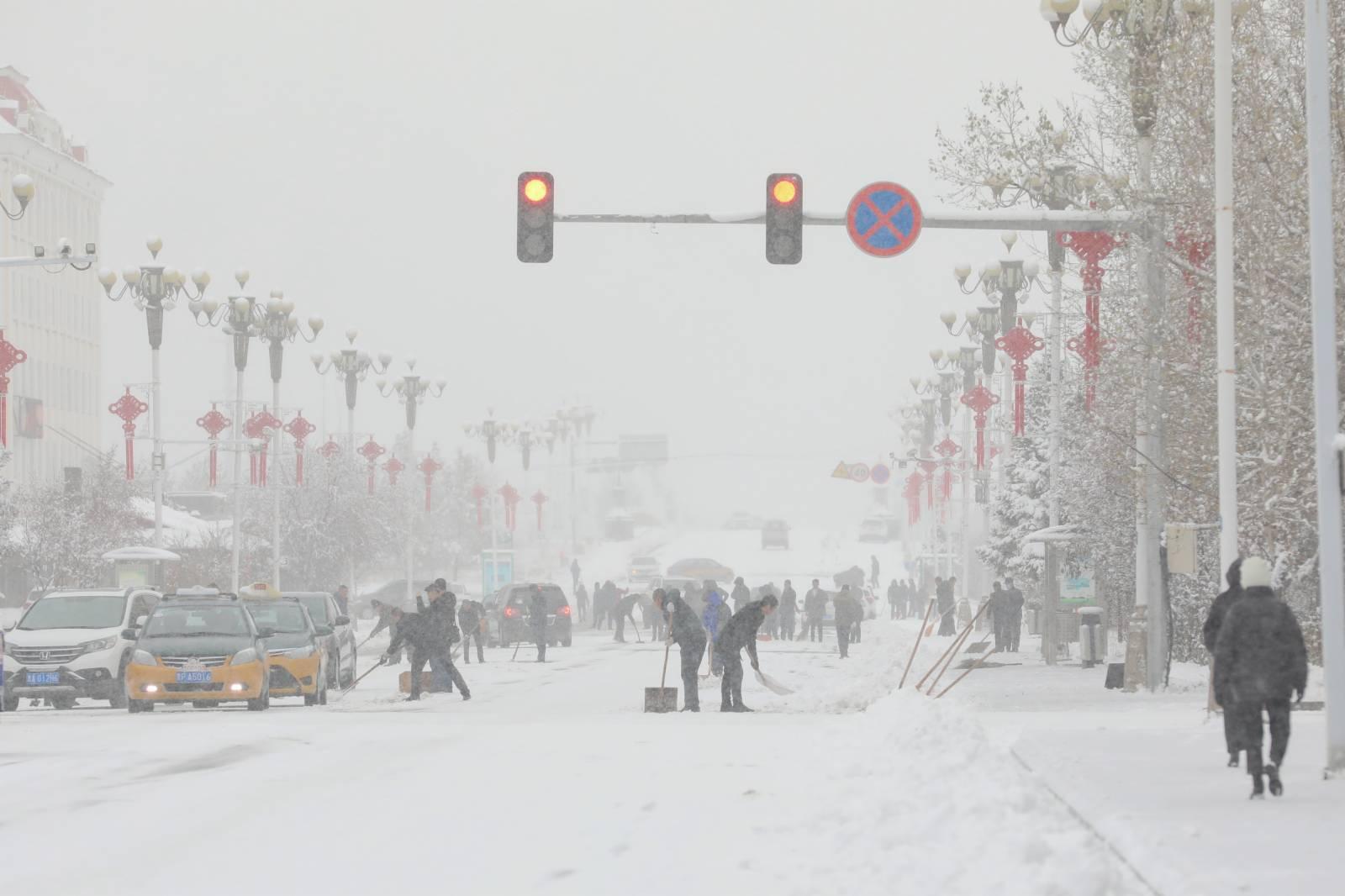 10月27日,黑龍江漠河市民在清理冰雪路面。(中新社)