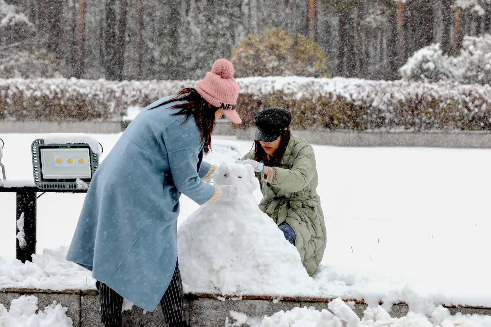 10月27日,黑龍江漠河,兩名女子在雪中堆雪人。(中新社)