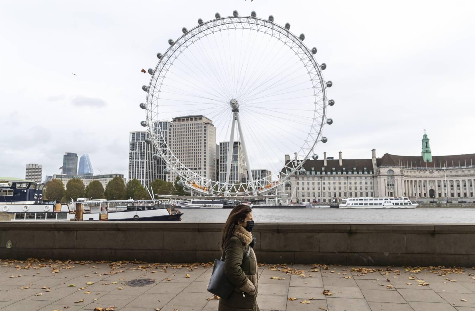 10月28日,一名戴口罩的女子在英國倫敦泰晤士河畔行走。(新華社)
