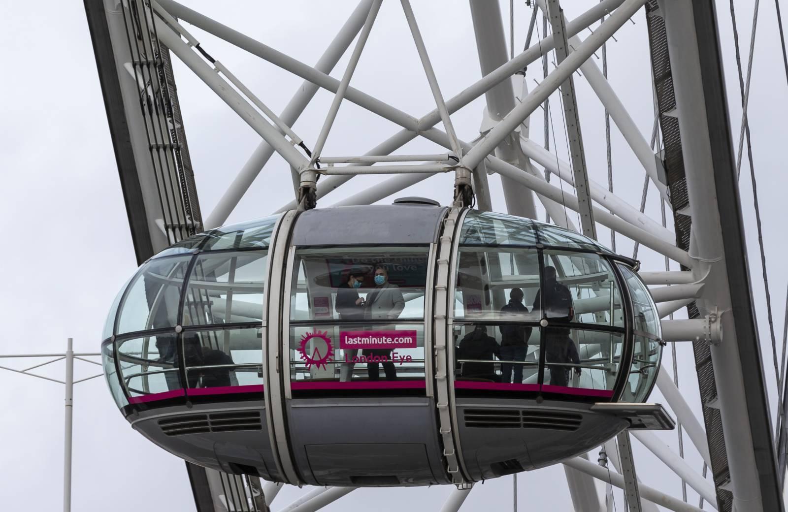 10月28日,戴口罩的遊客在英國倫敦乘坐摩天輪「倫敦眼」。(新華社)