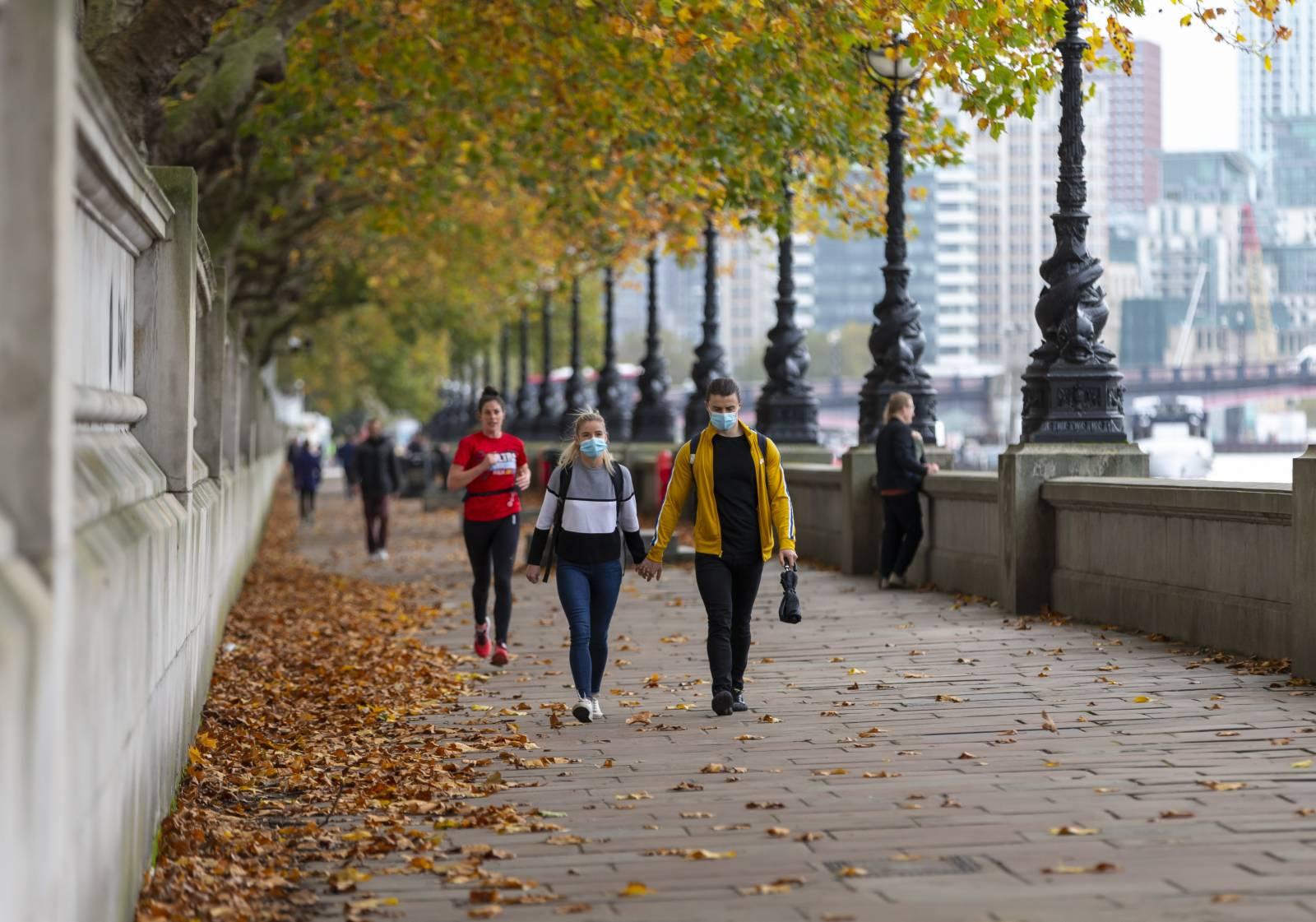 10月28日,戴口罩的人們在英國倫敦泰晤士河畔行走。(新華社)