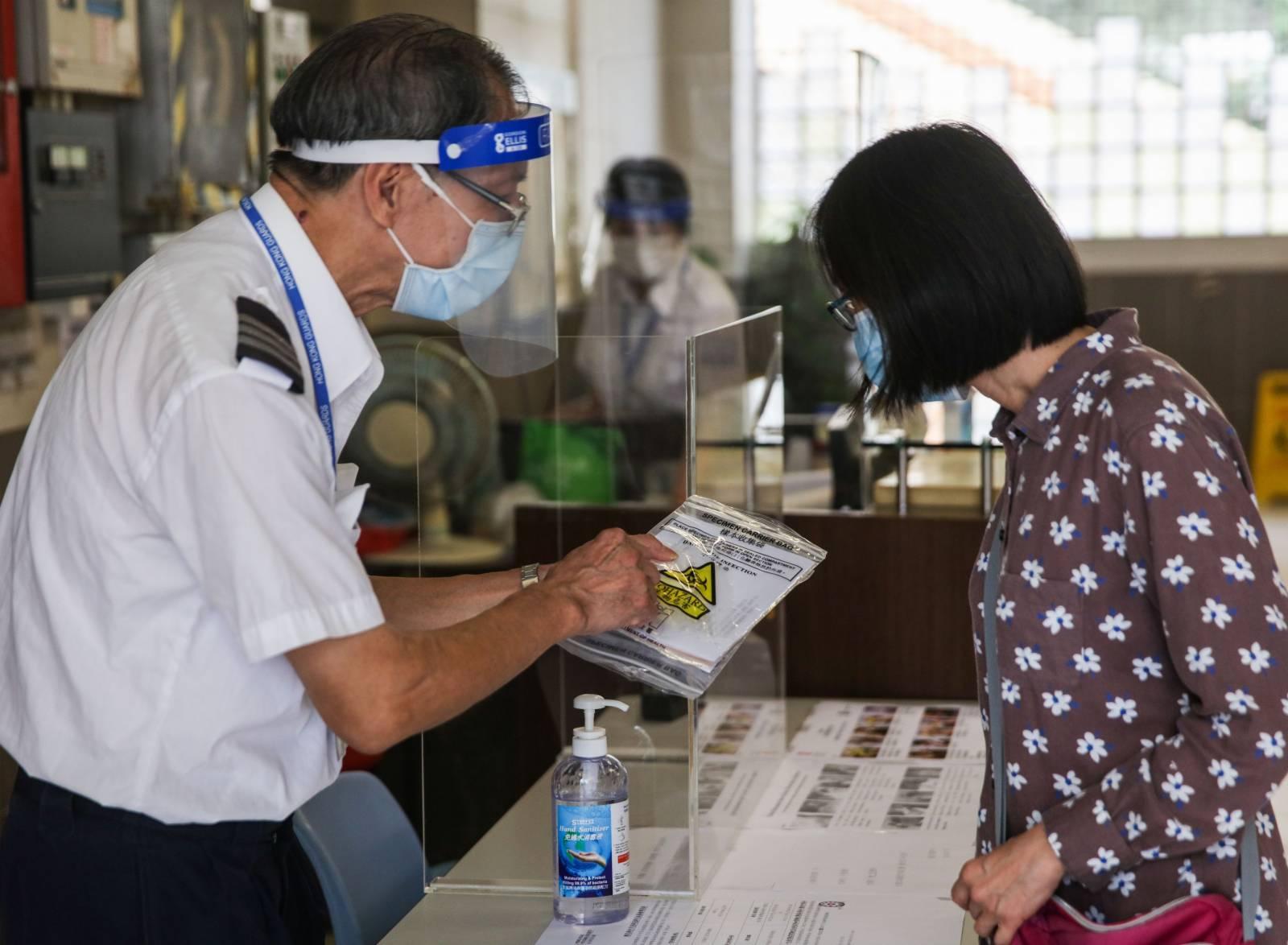 香港新增3宗確診個案,當中1宗本地個案患者50歲女子,居於土瓜灣樂民新村樂智樓。衞生署今日向居民內派樣本瓶做測試。(大公文匯全媒體記者 攝)