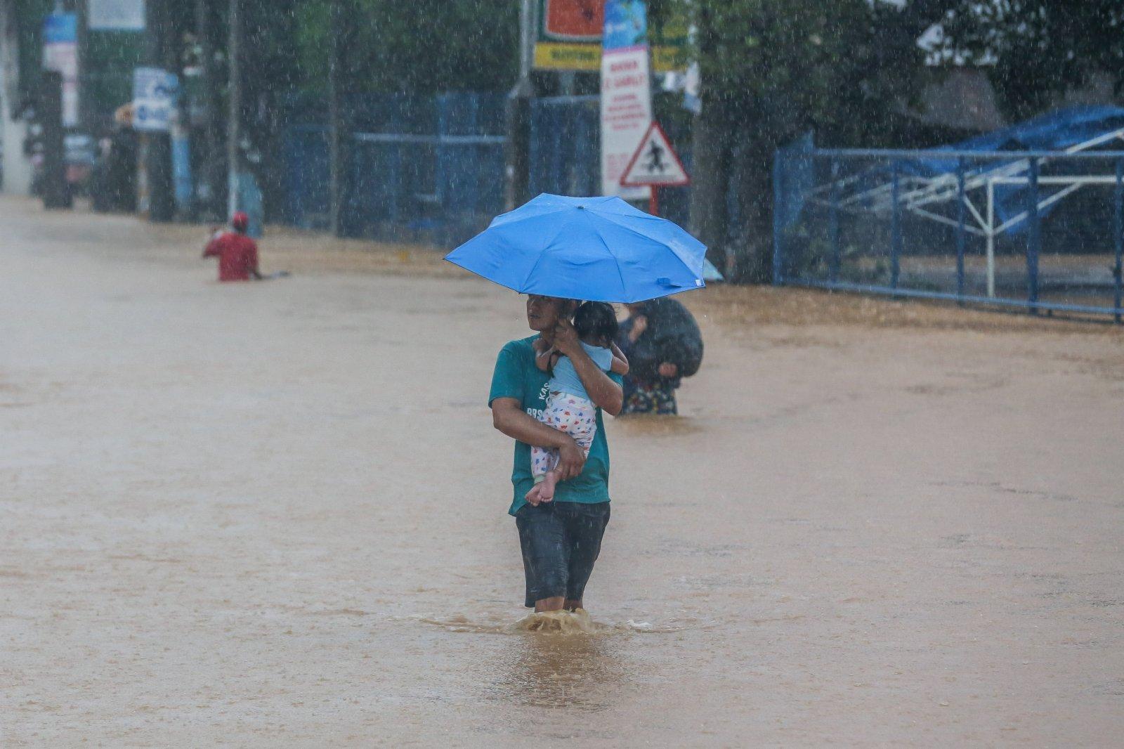 11月12日,在菲律賓黎剎省,當地居民在洪水中前行。(新華網)