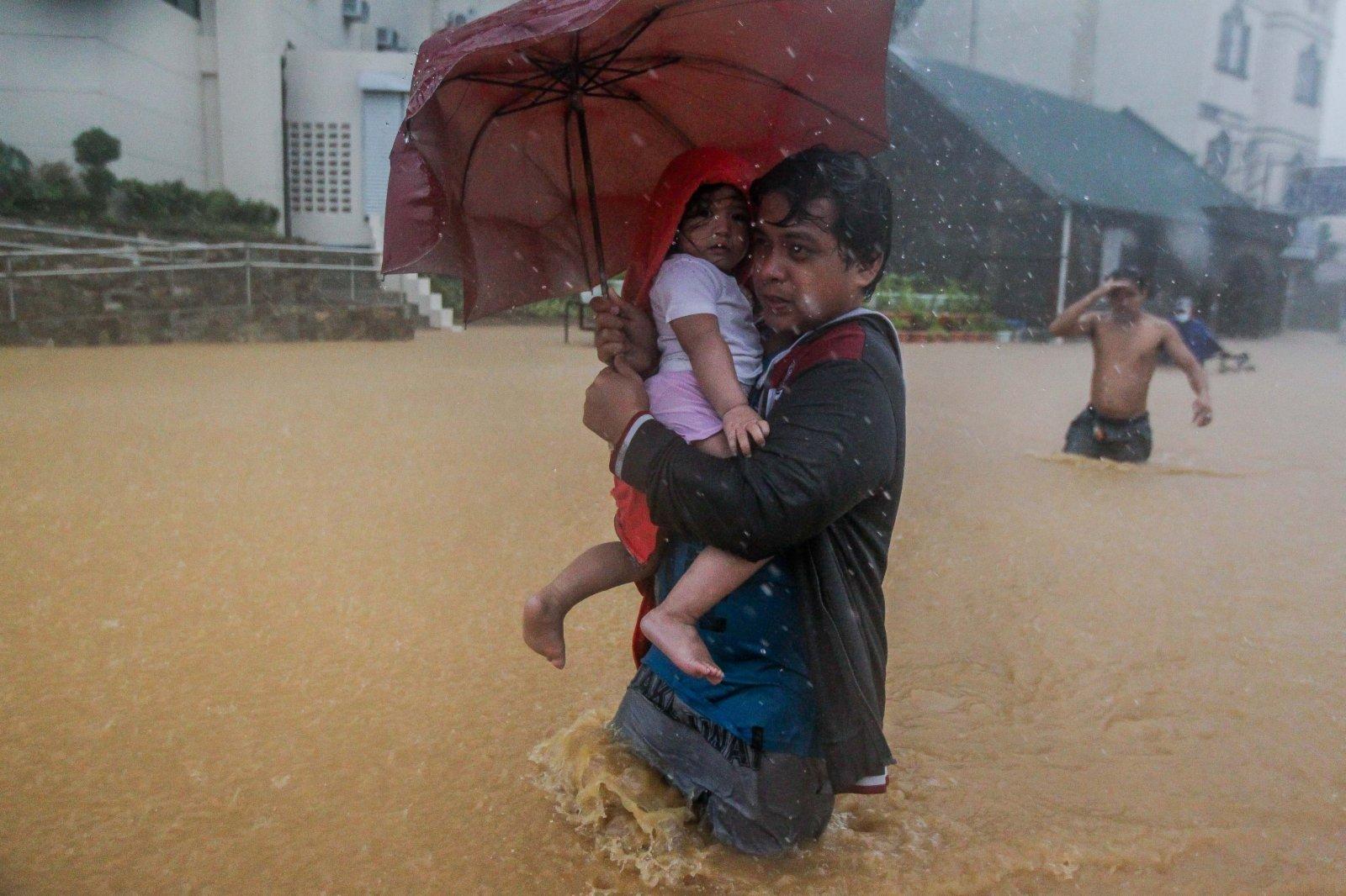 11月12日,在菲律賓馬尼拉,當地居民在洪水中前行。