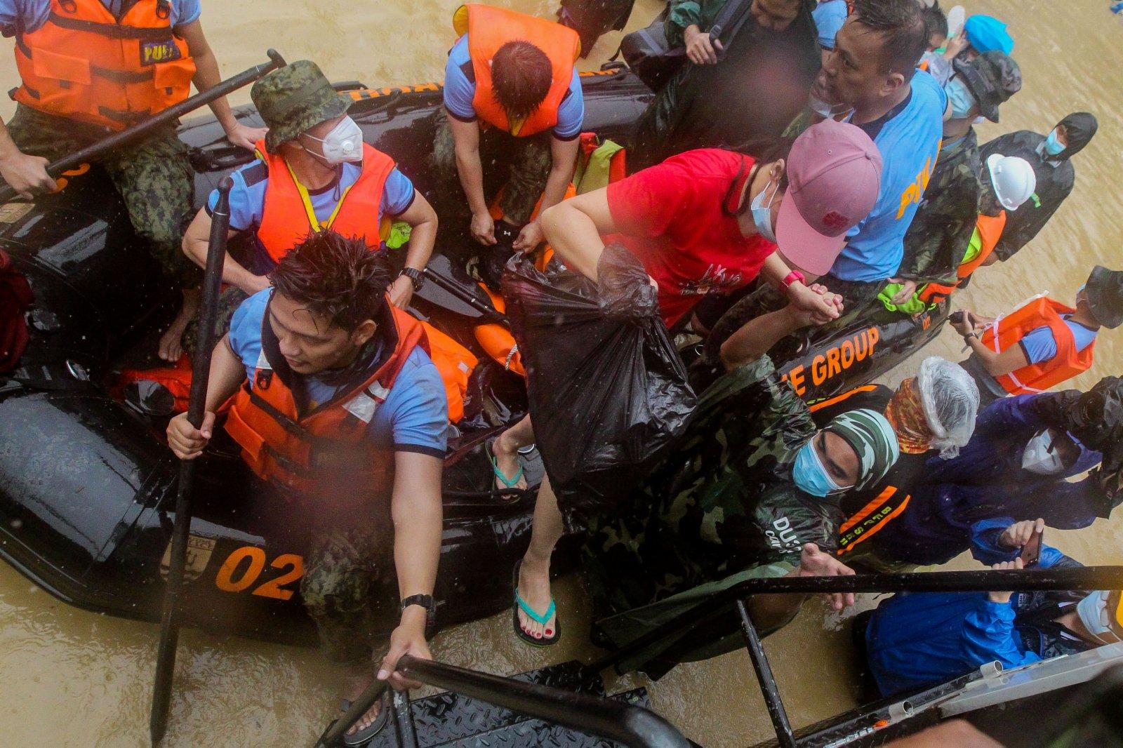 11月12日,在菲律賓馬尼拉,救援人員幫助被洪水圍困的居民轉移。(新華網)