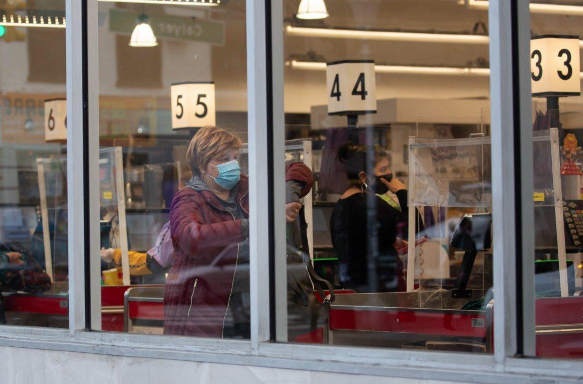 11月12日,在美國紐約一家超市,人們在裝有防護罩的收銀台前結賬。(新華社)