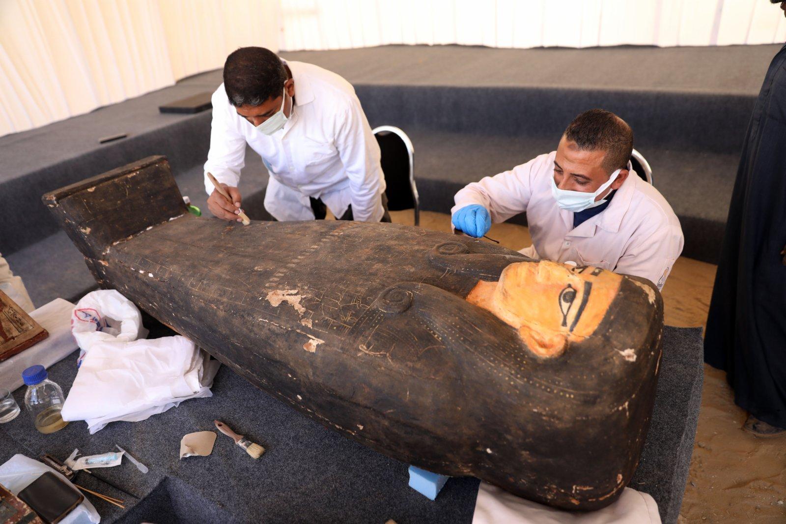 11月14日,在埃及吉薩,考古工作人員清理一具彩繪木棺。(新華社)