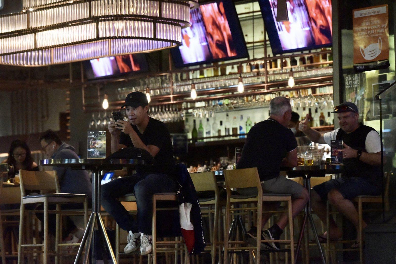 16日起再度收緊社交距離限制措施,酒吧每枱人數上限減至兩人。圖為中環蘭桂坊,市民正在消遣。 (中新社)