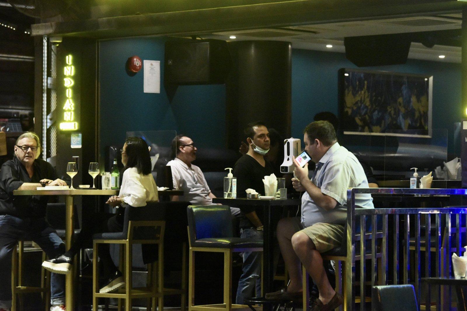 16日起再度收緊社交距離限制措施,酒吧每枱人數上限減至兩人。圖為中環蘭桂坊,市民正在消遣。(中新社)