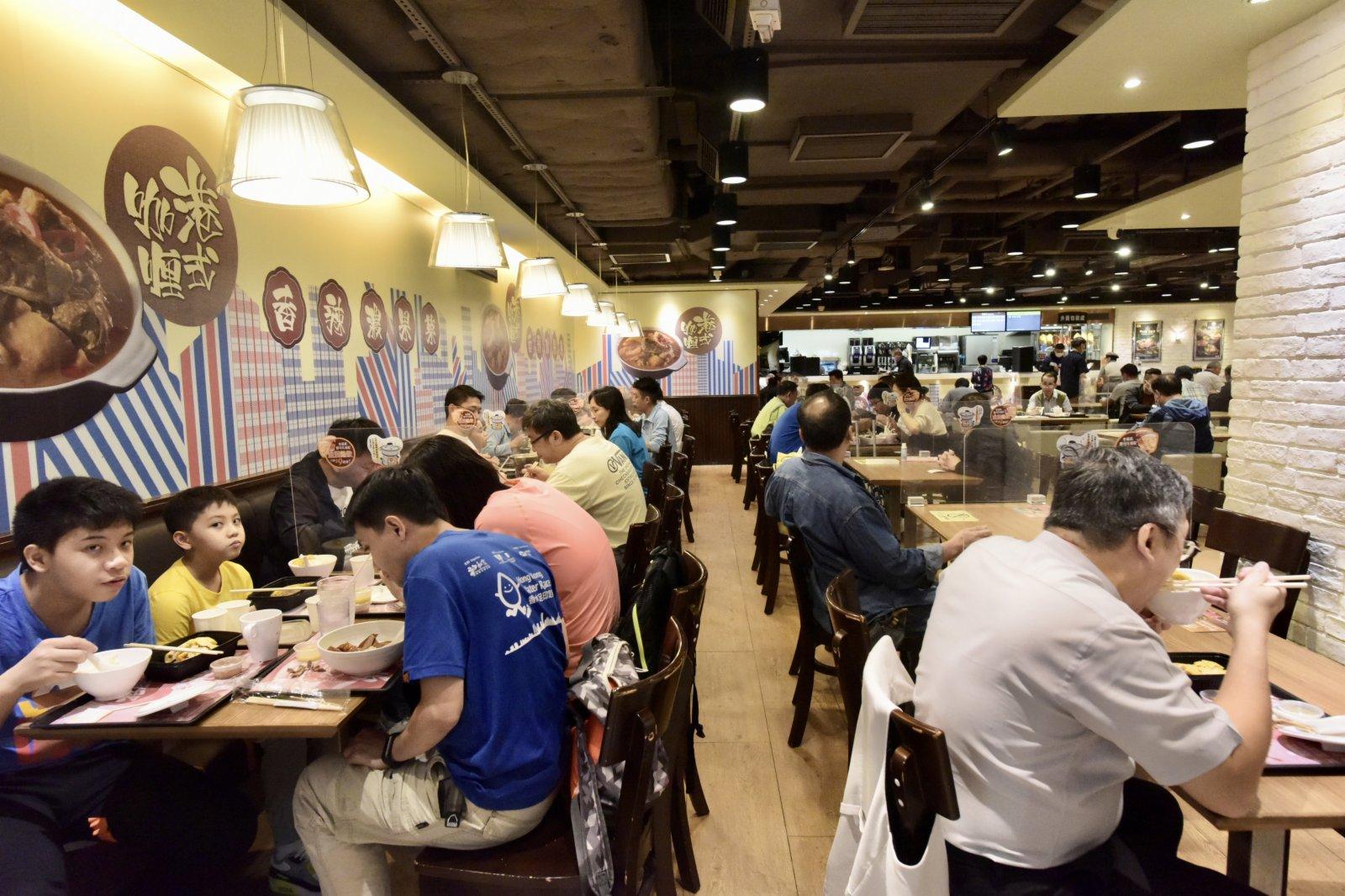 16日起再度收緊社交距離限制措施,食肆每枱人數上限會由現時的六人縮減至四人。圖為金鐘一食肆,市民正在用餐。(中新社)