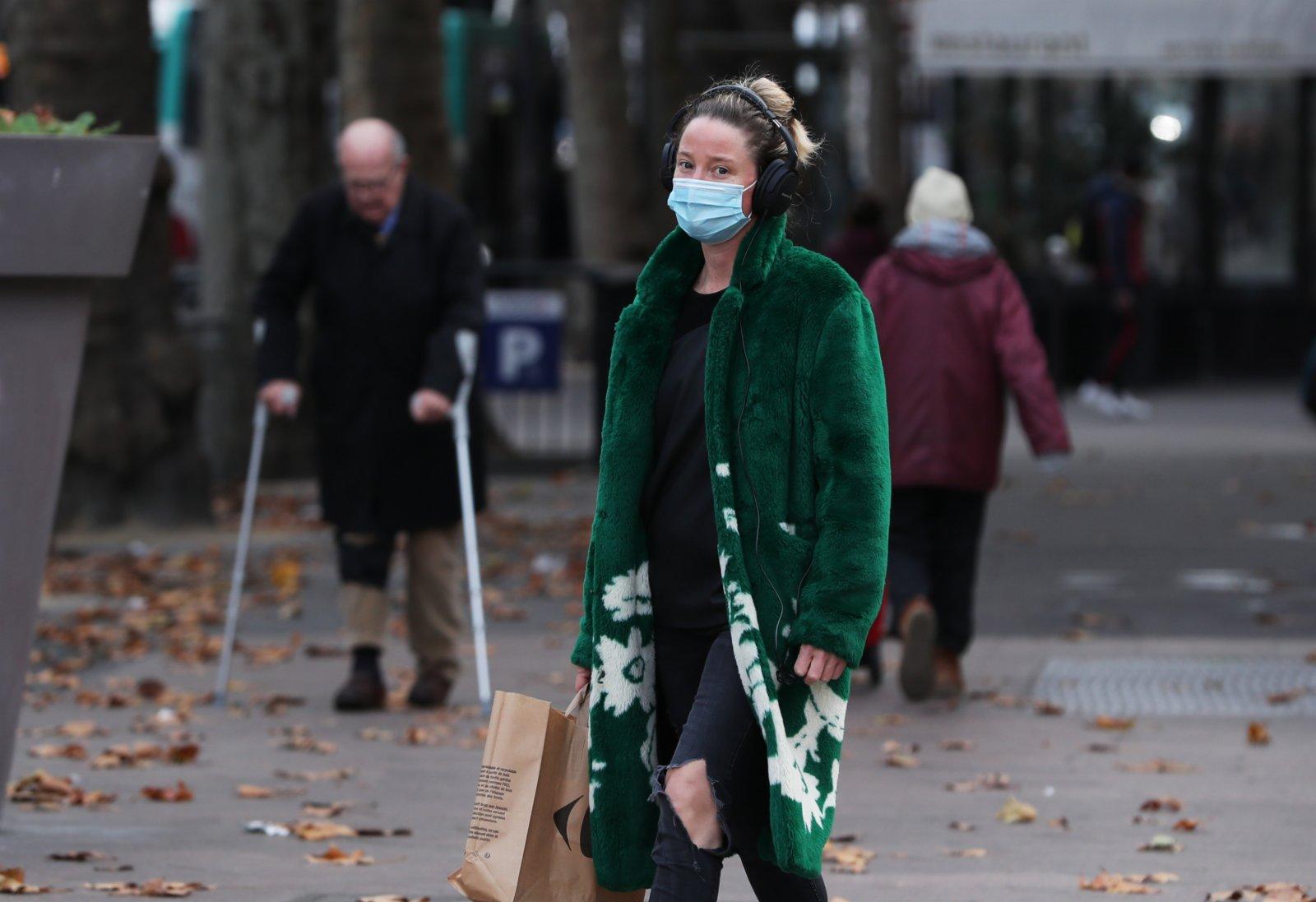 11月16日,一名女子戴口罩走在法國巴黎聖米歇爾廣場附近。