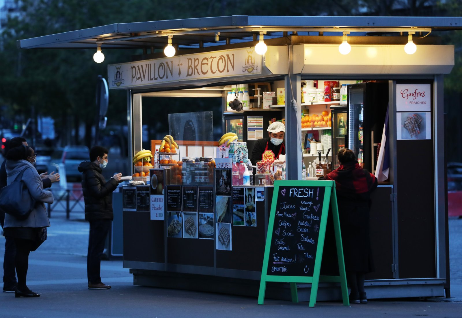 11月16日,人們在法國巴黎街頭的食品攤前排隊。