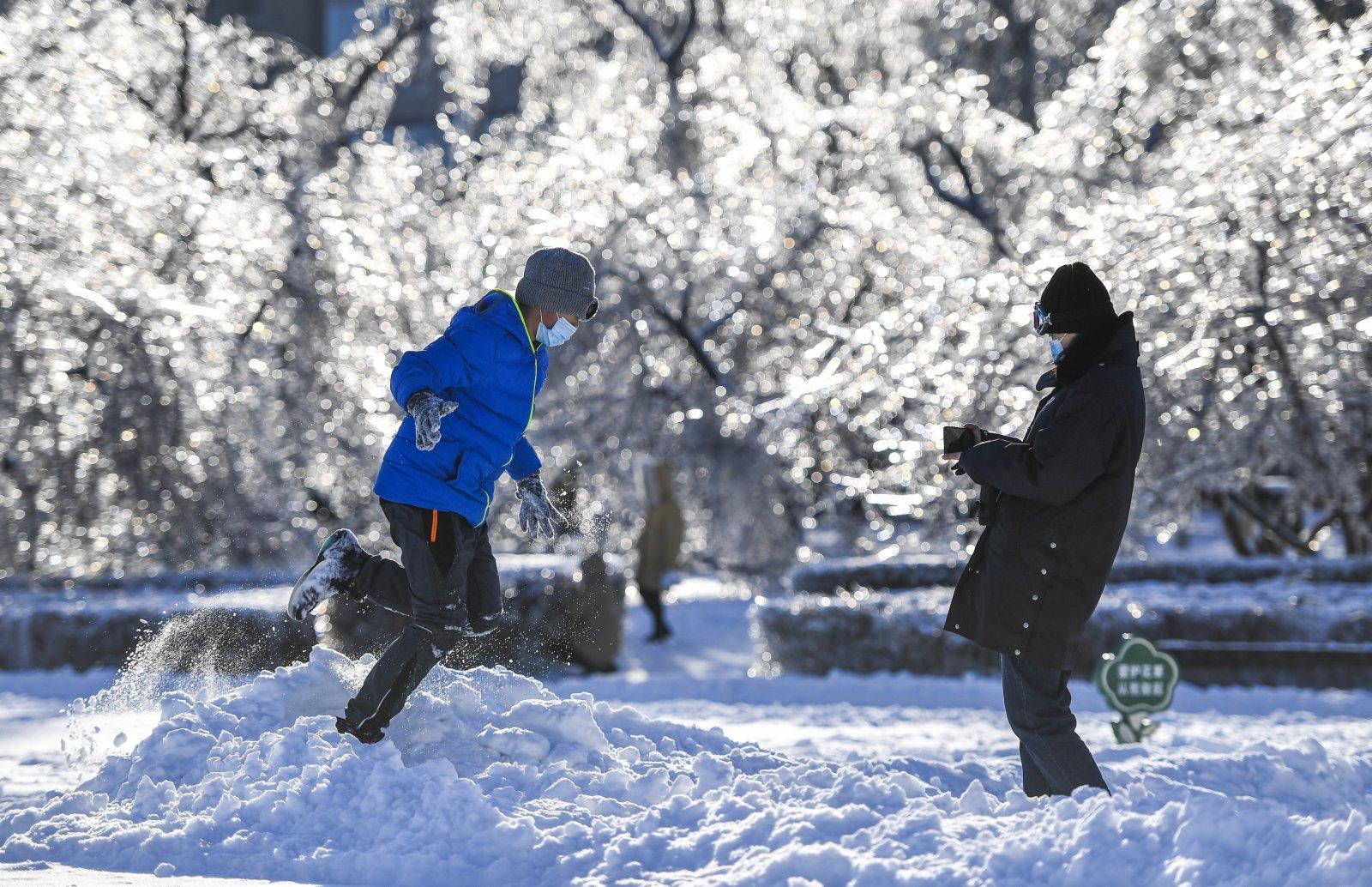 市民在長春市文化廣場雪地中玩耍。