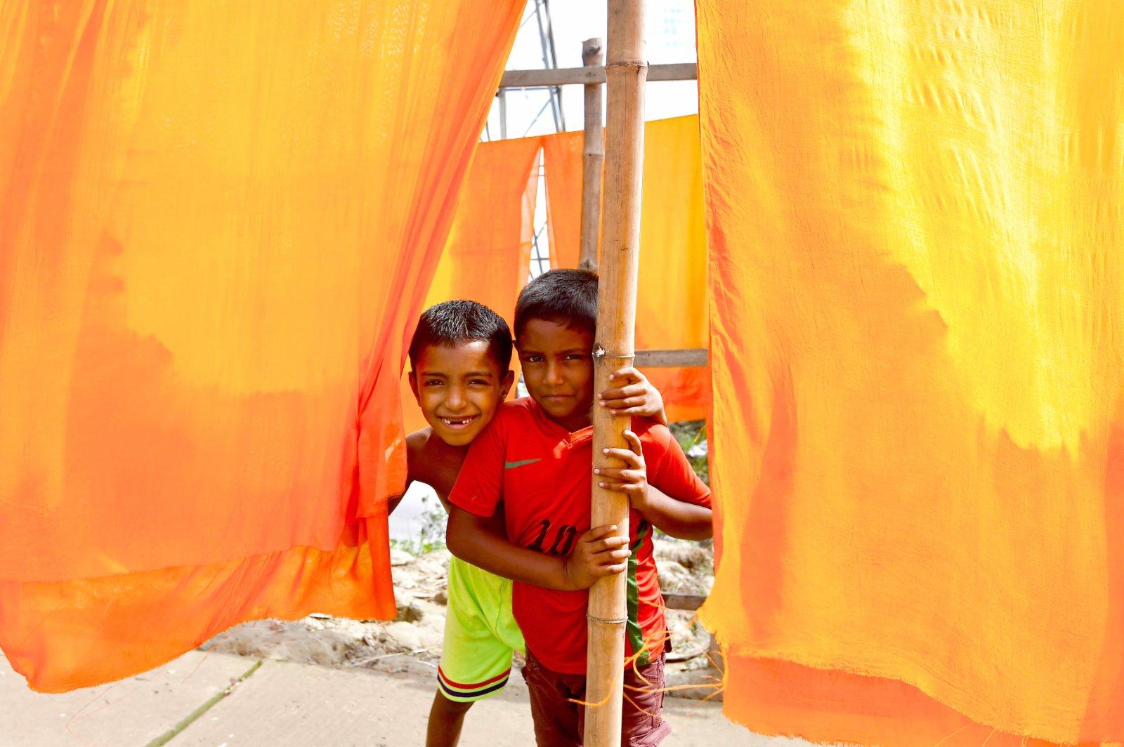 9月15日,在孟加拉國納拉揚甘傑地區,兩名兒童站在晾曬的布匹旁。(新華社)