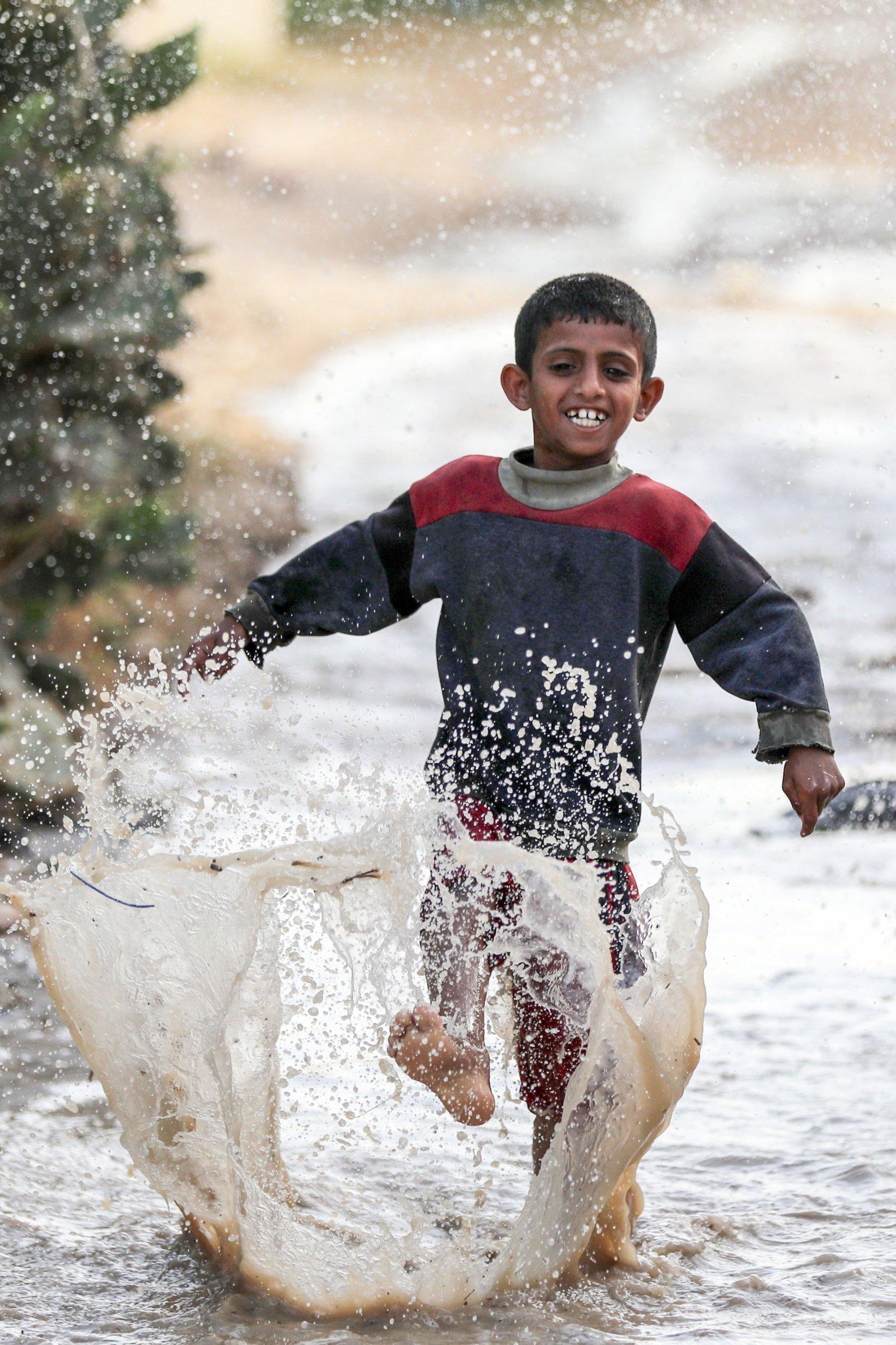 5月19日,加沙地帶的汗尤尼斯迎來高溫天氣,巴勒斯坦男孩在一處水坑中嬉戲。(新華社)