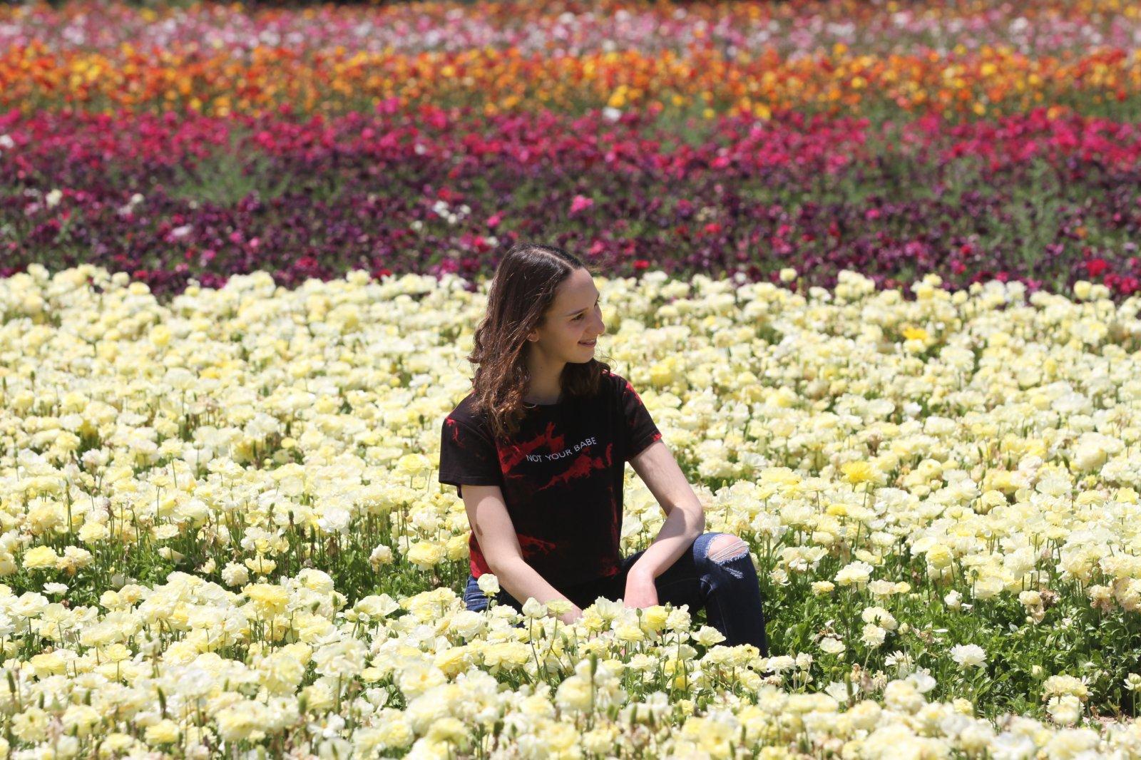 5月1日,在以色列南部的尼爾伊扎克集體農場,一名女孩在花田中留影。(新華社)