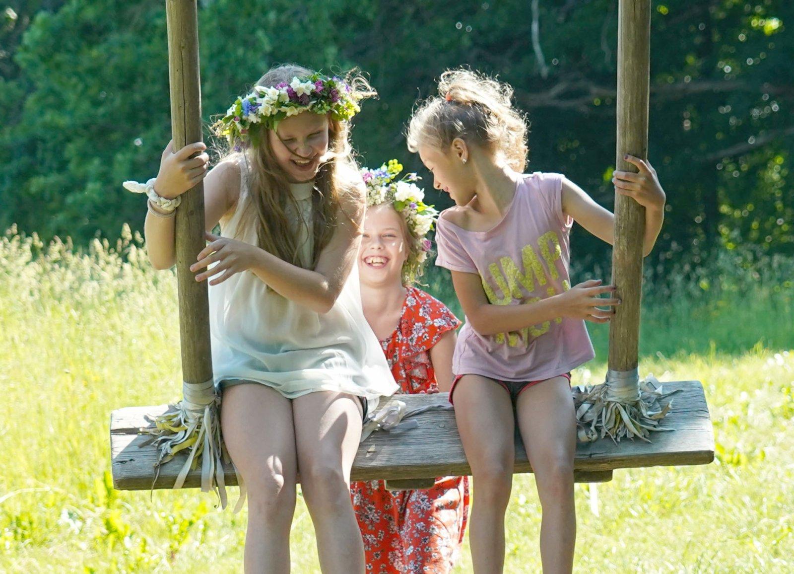 6月21日,頭戴花冠的女孩們在拉脫維亞鄉村增特內的草坪上玩耍。(新華社)
