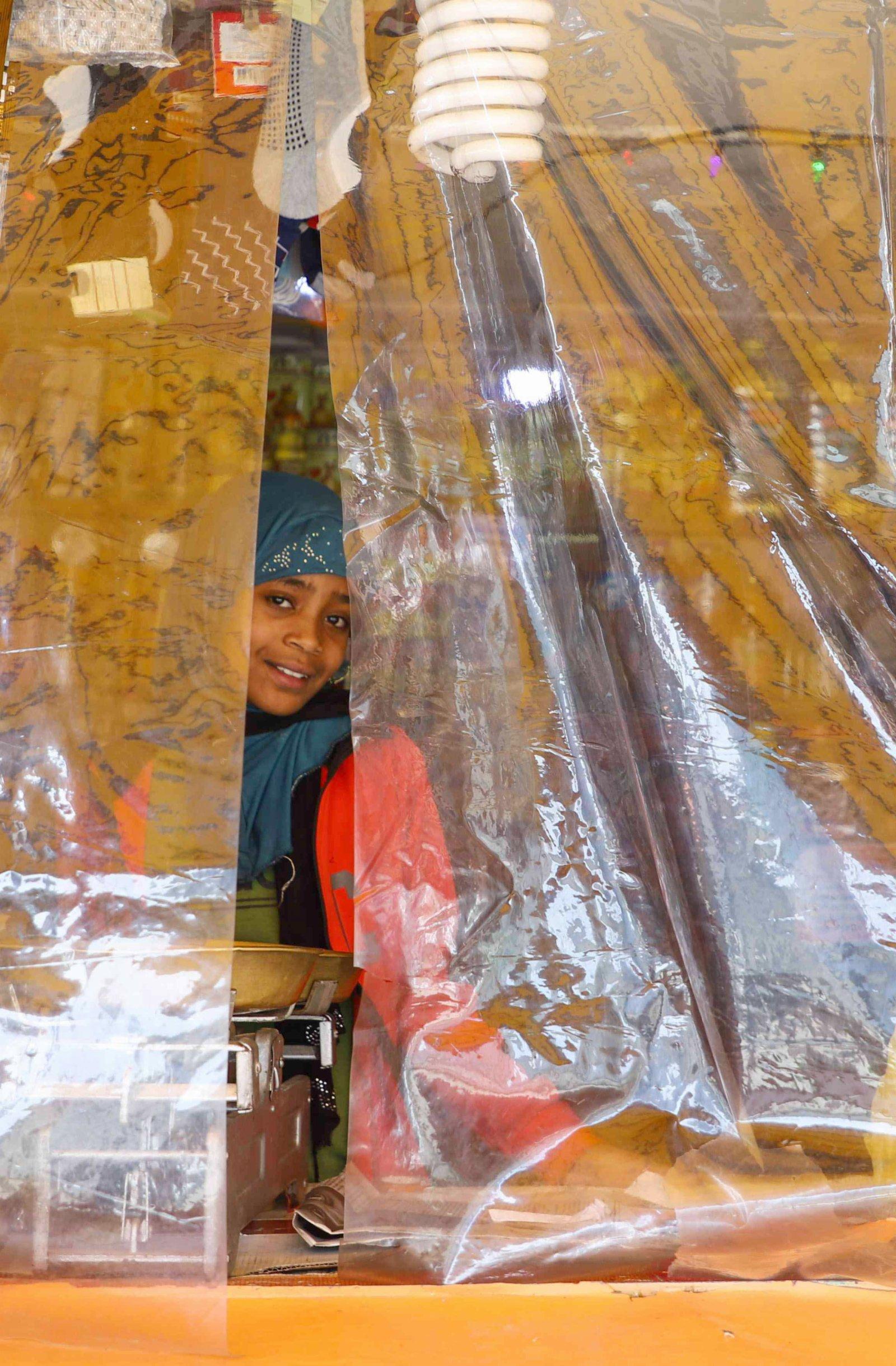 8月14日,在埃塞俄比亞首都亞的斯亞貝巴的一處店舖,一名小女孩透過被塑料膜遮擋的窗口向外張望。(新華社)