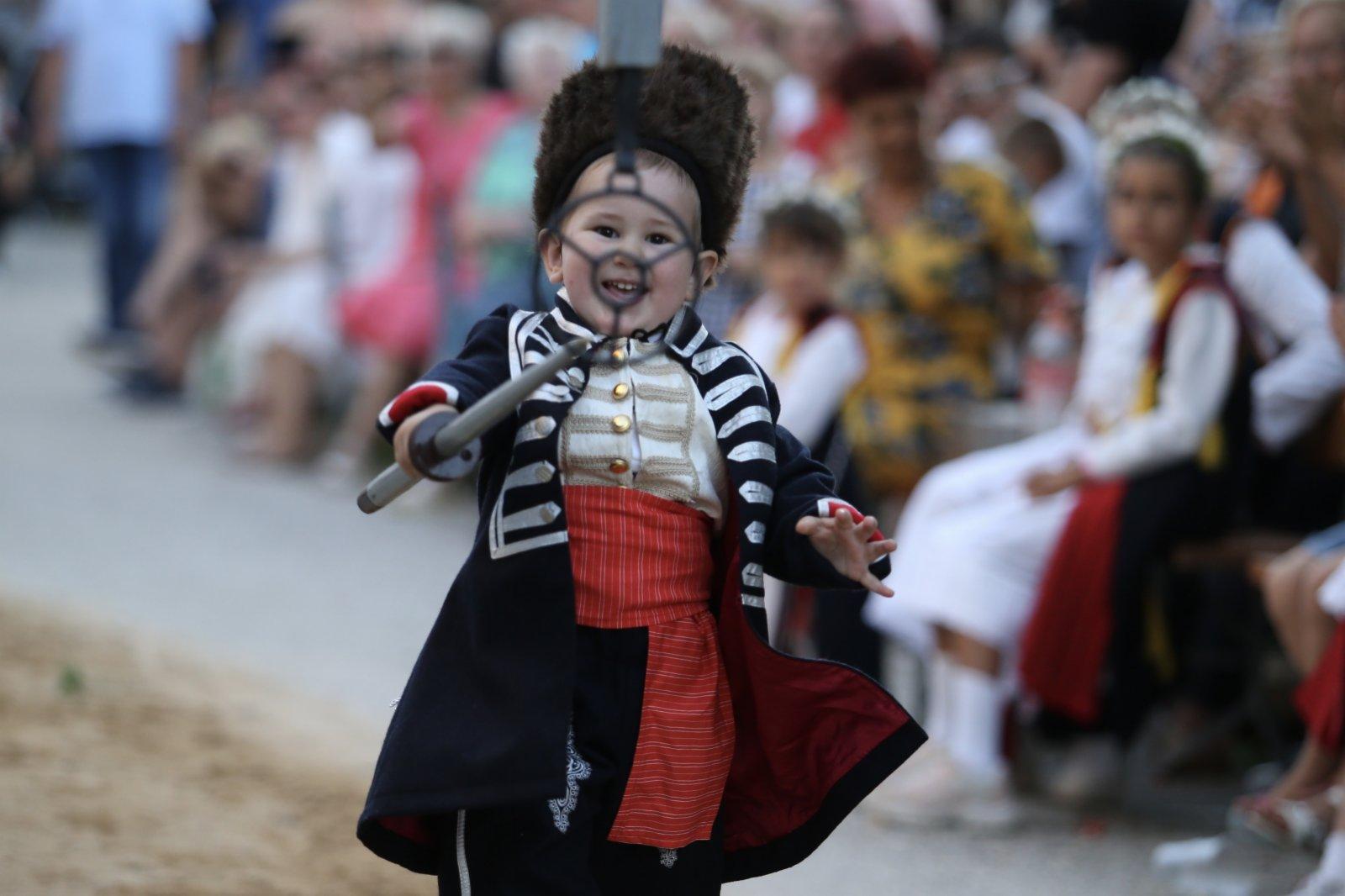 8月23日,在克羅地亞南部小城錫尼附近的伯內茲村,身著傳統服裝的兒童參加兒童長矛射環比賽。(新華社)