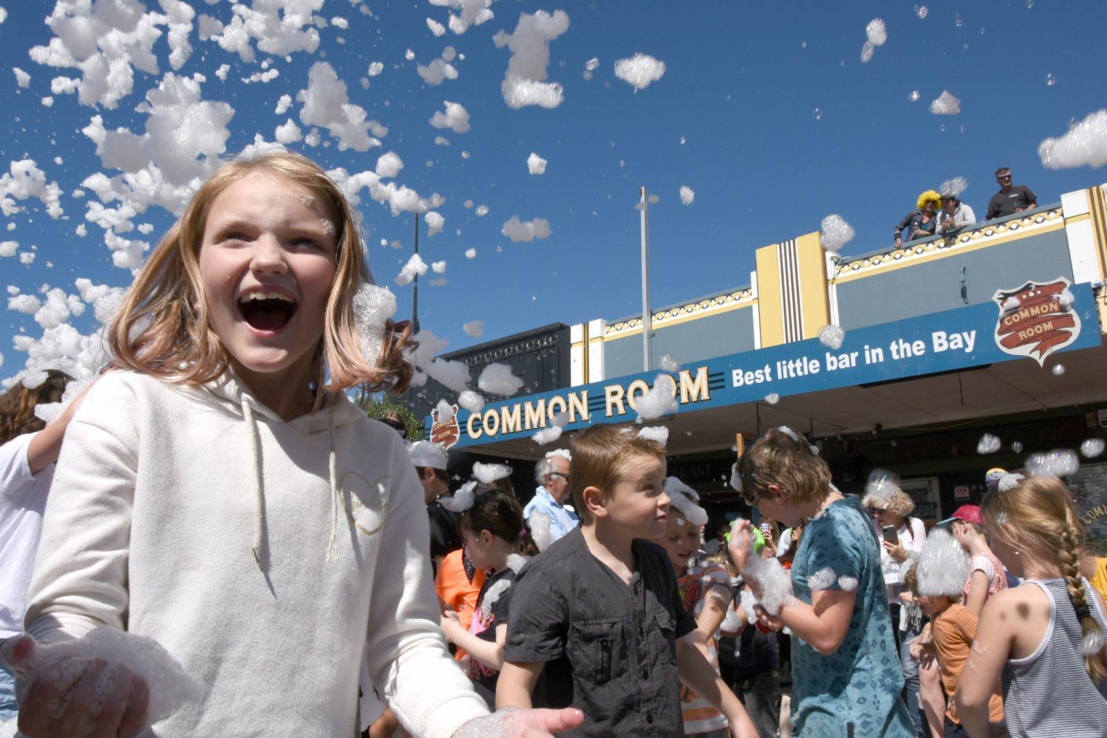 10月3日,在新西蘭黑斯廷斯,兒童在花車吹出的泡沫中嬉戲。(新華社)