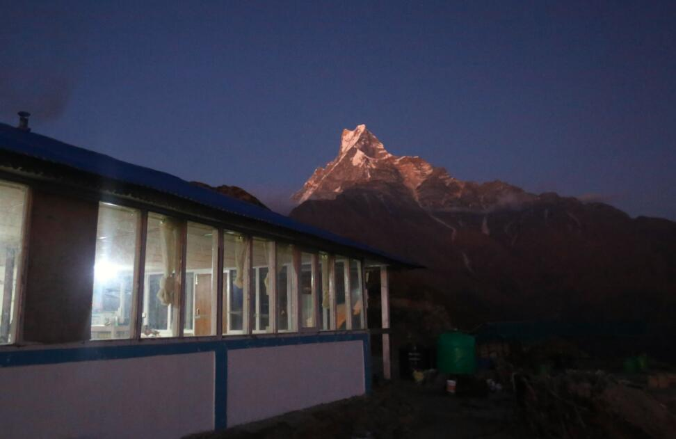 這是11月10日在尼泊爾安納布爾納地區拍攝的魚尾峰和一家客棧。(新華社)