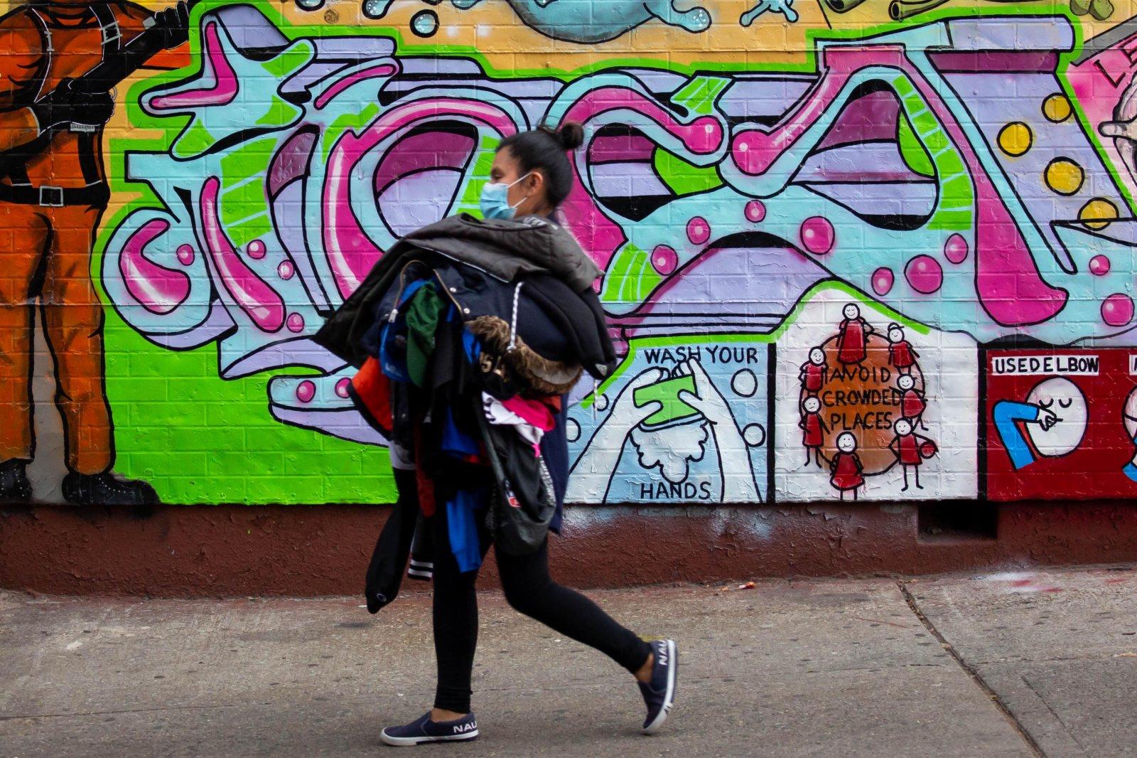 美國約翰斯·霍普金斯大學21日發布的新冠疫情最新統計數據顯示,美國累計確診病例超過1200萬例。11月21日,在美國紐約,一名女子走過抗疫宣傳壁畫。(新華社)