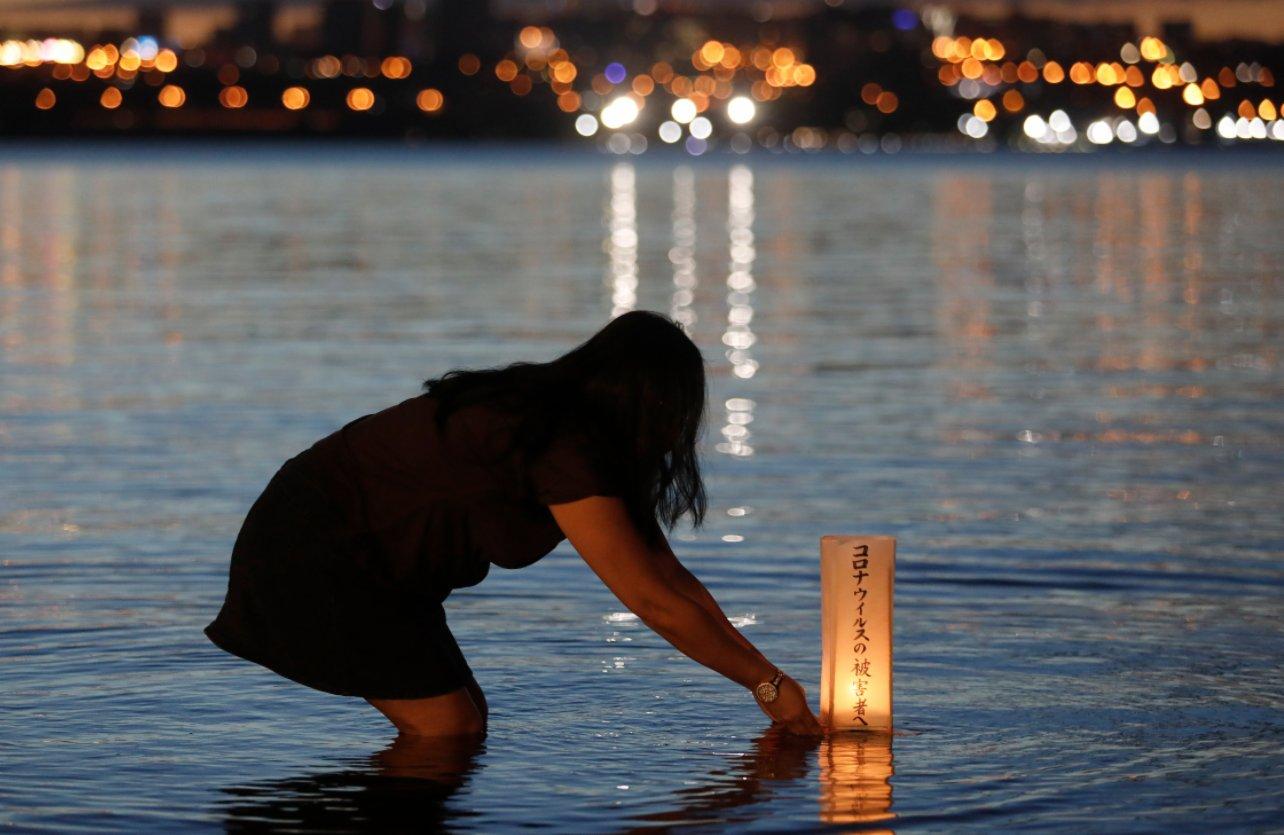 11月30日,在巴西首都巴西利亞,一名女子往湖中放入水燈。(新華社)