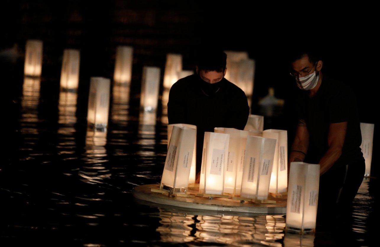 11月30日,在巴西首都巴西利亞,兩名男子往湖中放入水燈。(新華社)