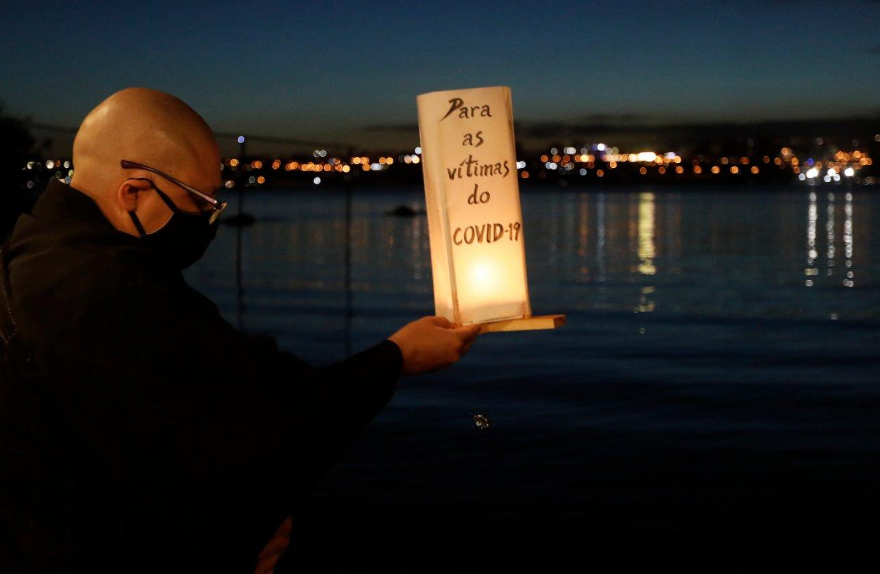 11月30日,在巴西首都巴西利亞,一名男子往湖中放入水燈,上面用葡萄牙文寫著「獻給新冠逝者」。(新華社)
