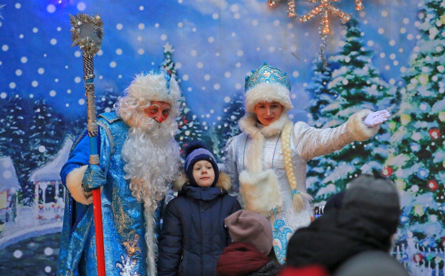 1月2日,在白俄羅斯首都明斯克,打扮成「嚴寒老人」和「雪姑娘」形象的演員在兒童鐵路一處車站與一名兒童合影。(新華社)