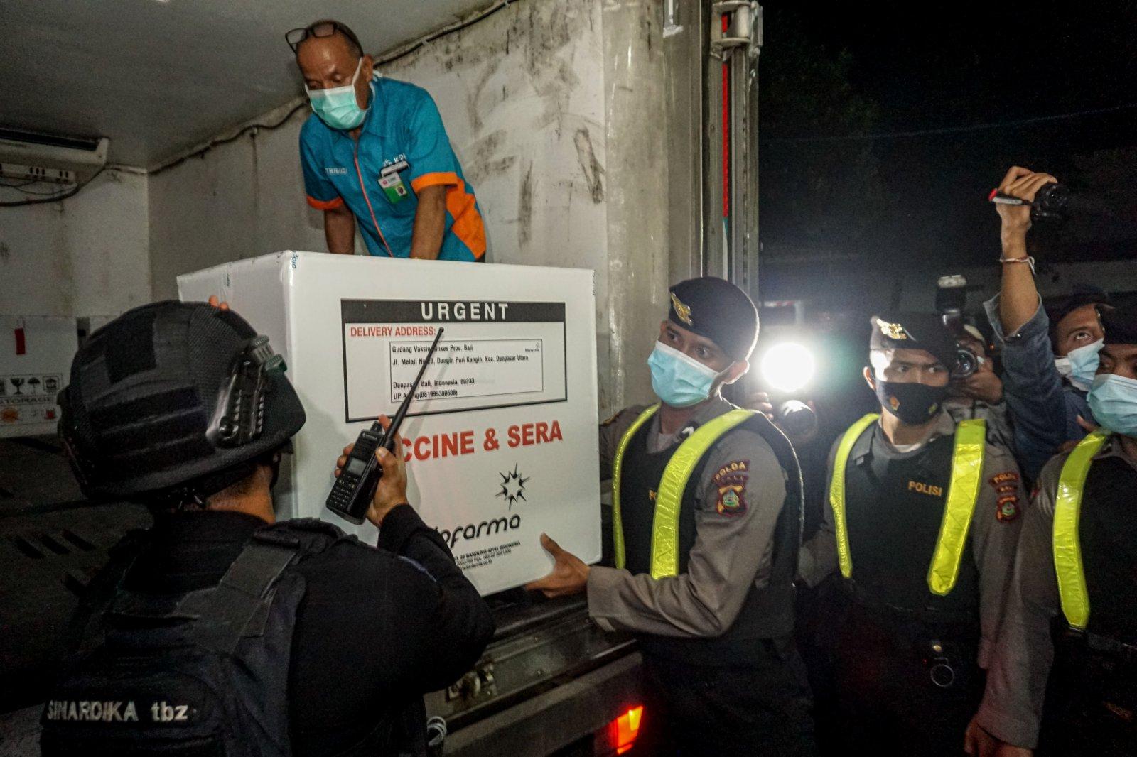 1月5日淩晨,在印度尼西亞巴厘省登巴薩市,人們搬運剛剛運抵的新冠疫苗。(新華社)