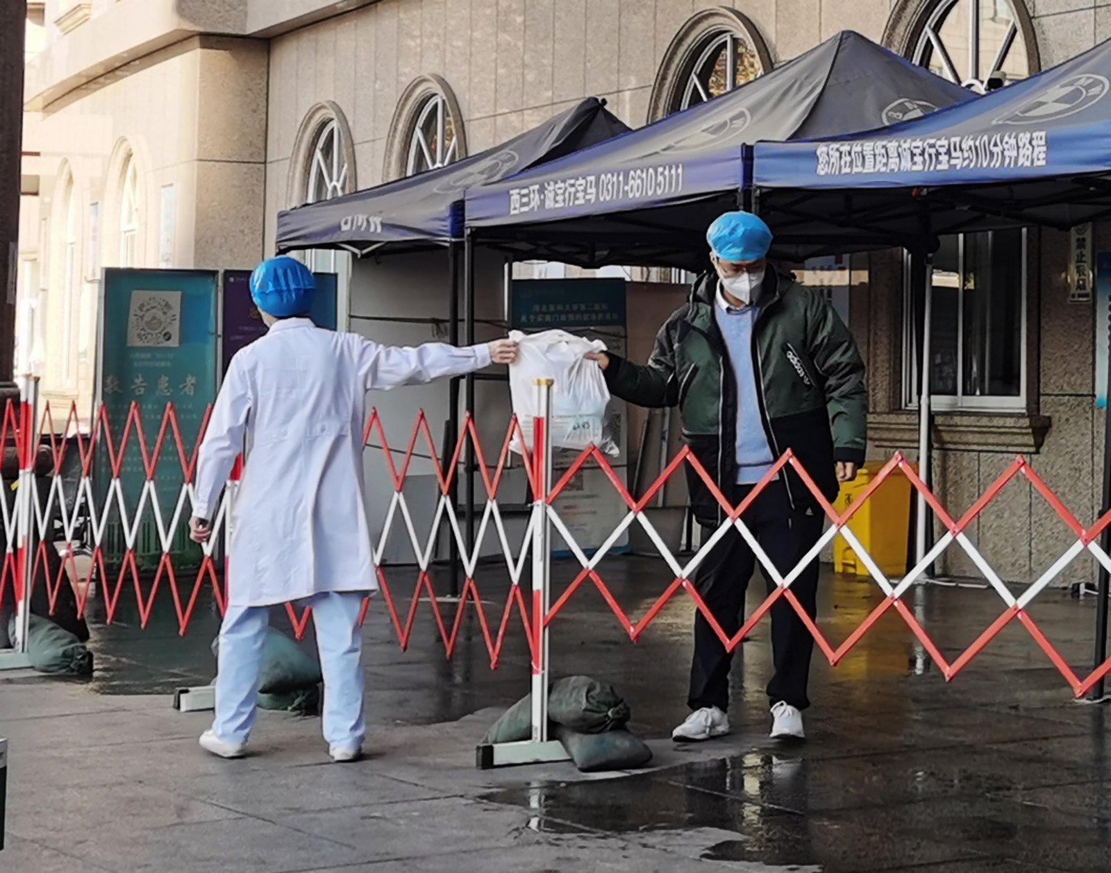 1月5日,河北醫科大學附屬第二醫院急診樓封閉,工作人員隔着圍欄交接物品。(中新社)