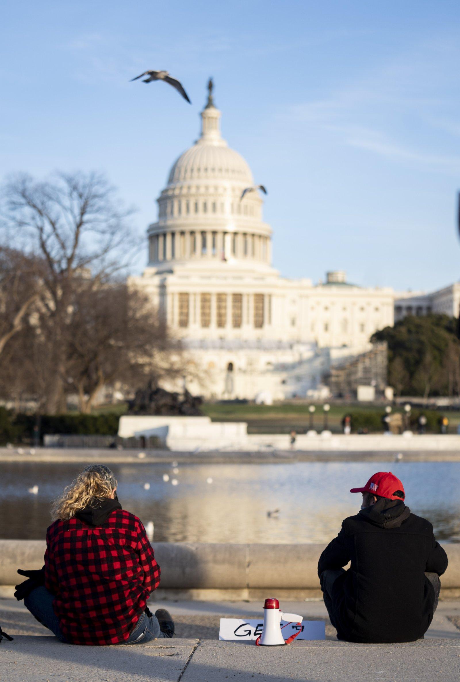 1月7日,在美國首都華盛頓,美國總統特朗普的支持者坐在國會大廈前。